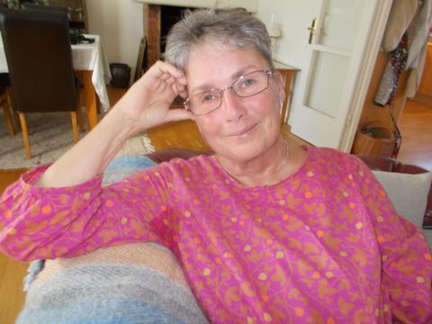 Bild tolkning: Helena har kortklippt hår, glasögon och bär en rosa Gudrun Sjödén tunika.