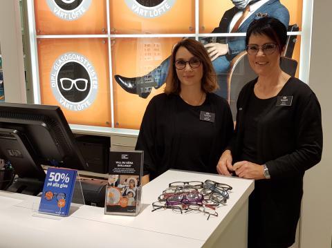 Carola Johnsson och Marie Burman står vid disken i butiken. Framför sig ligger en hög med begagnade glasögon.