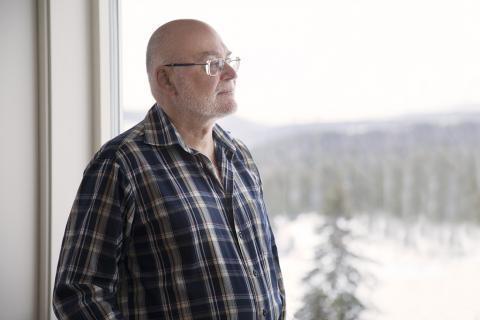 Gregor har snaggat grått hår, glasögon och ett blåvitrutig skjorta på sig. Han tittar ut genom fönstret på naturen utanför.