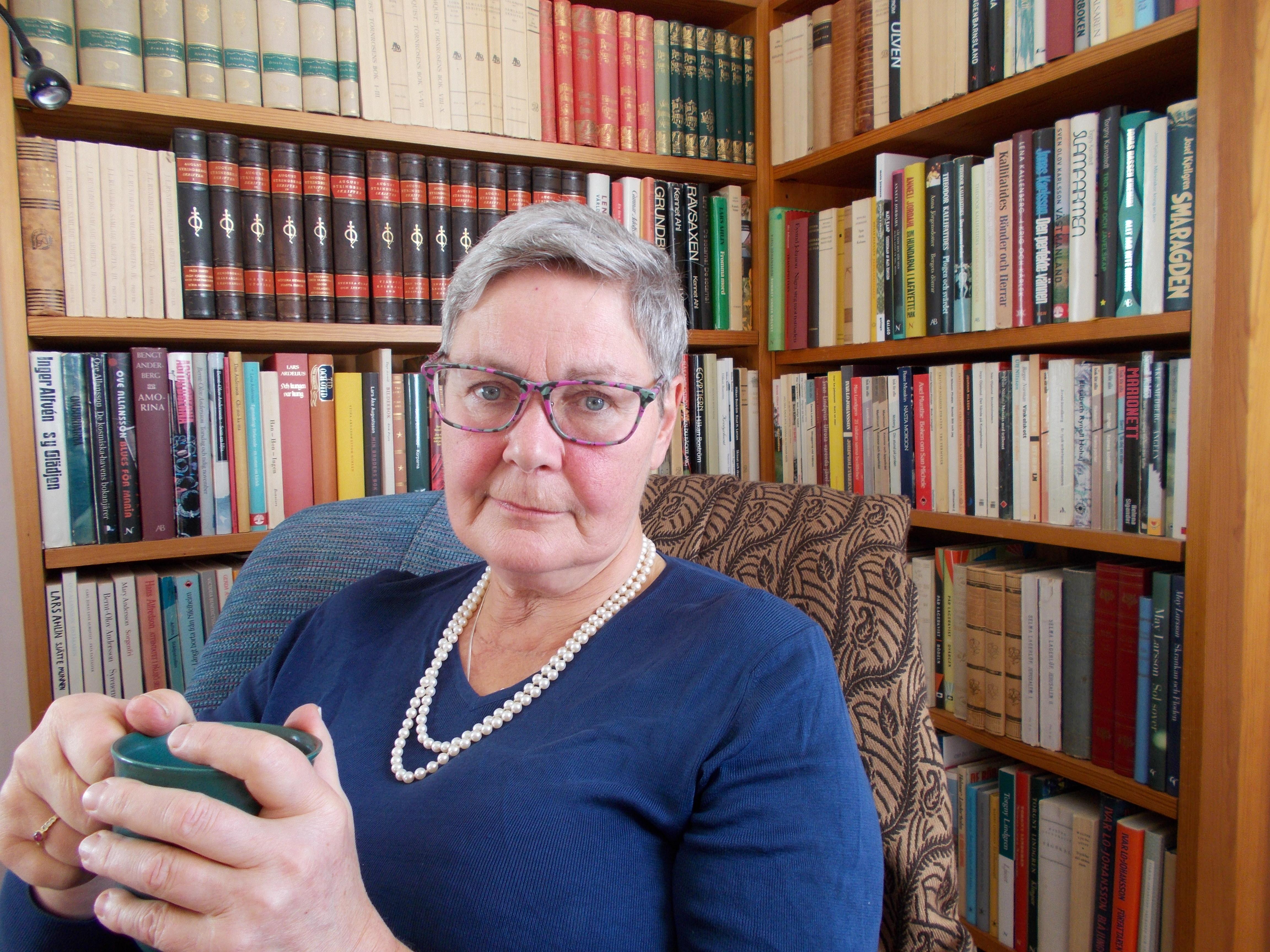 Maria sitter framför en bokhylla. Hon har grått hår, glasögon och en blå tröja och ett vitt halsband.