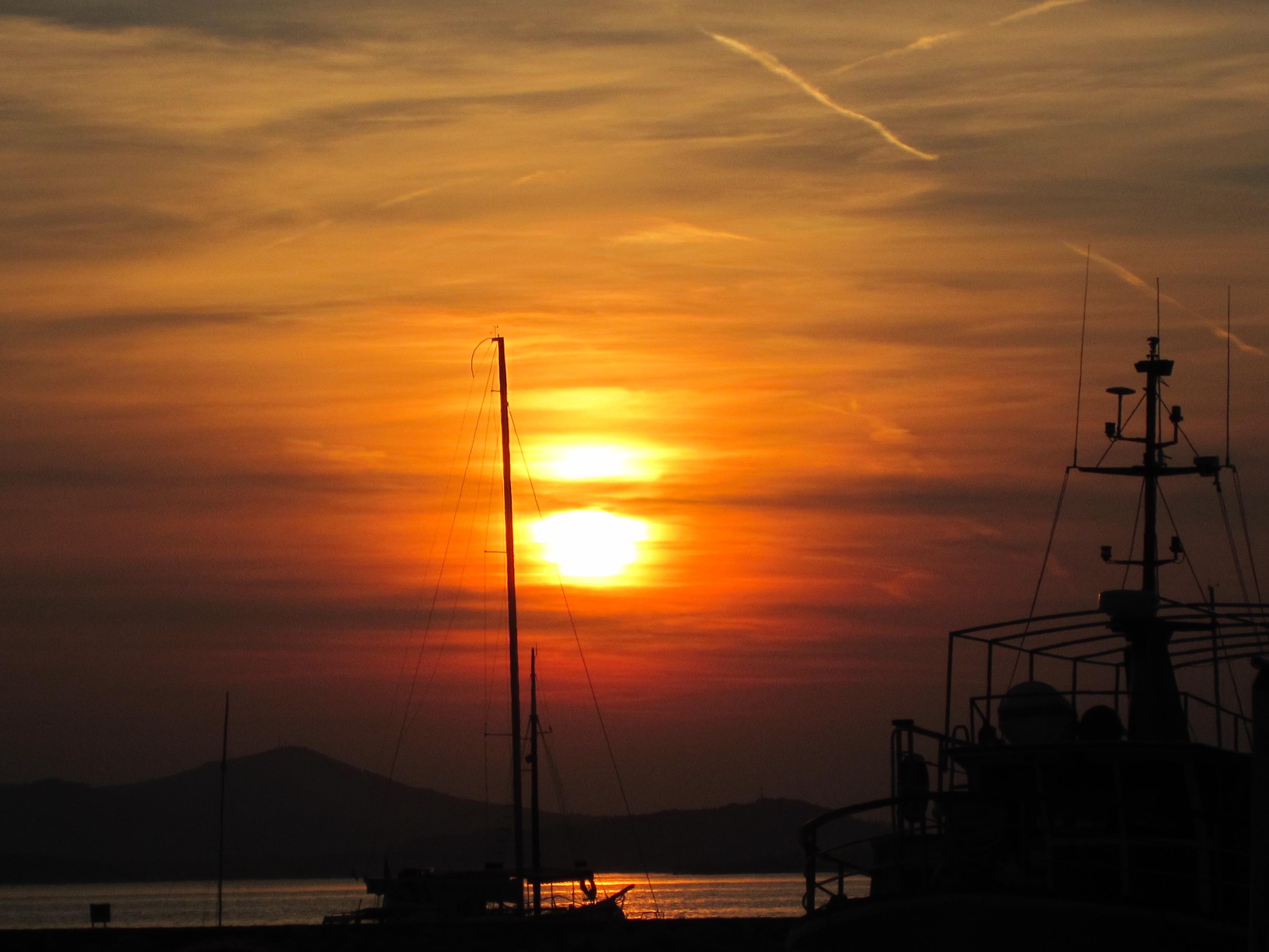 En solnedgång i skimrande gula nyanser där berg skymtar i bakgrunden och i förgrunden fiskebåtar och båtmasten vid kajen