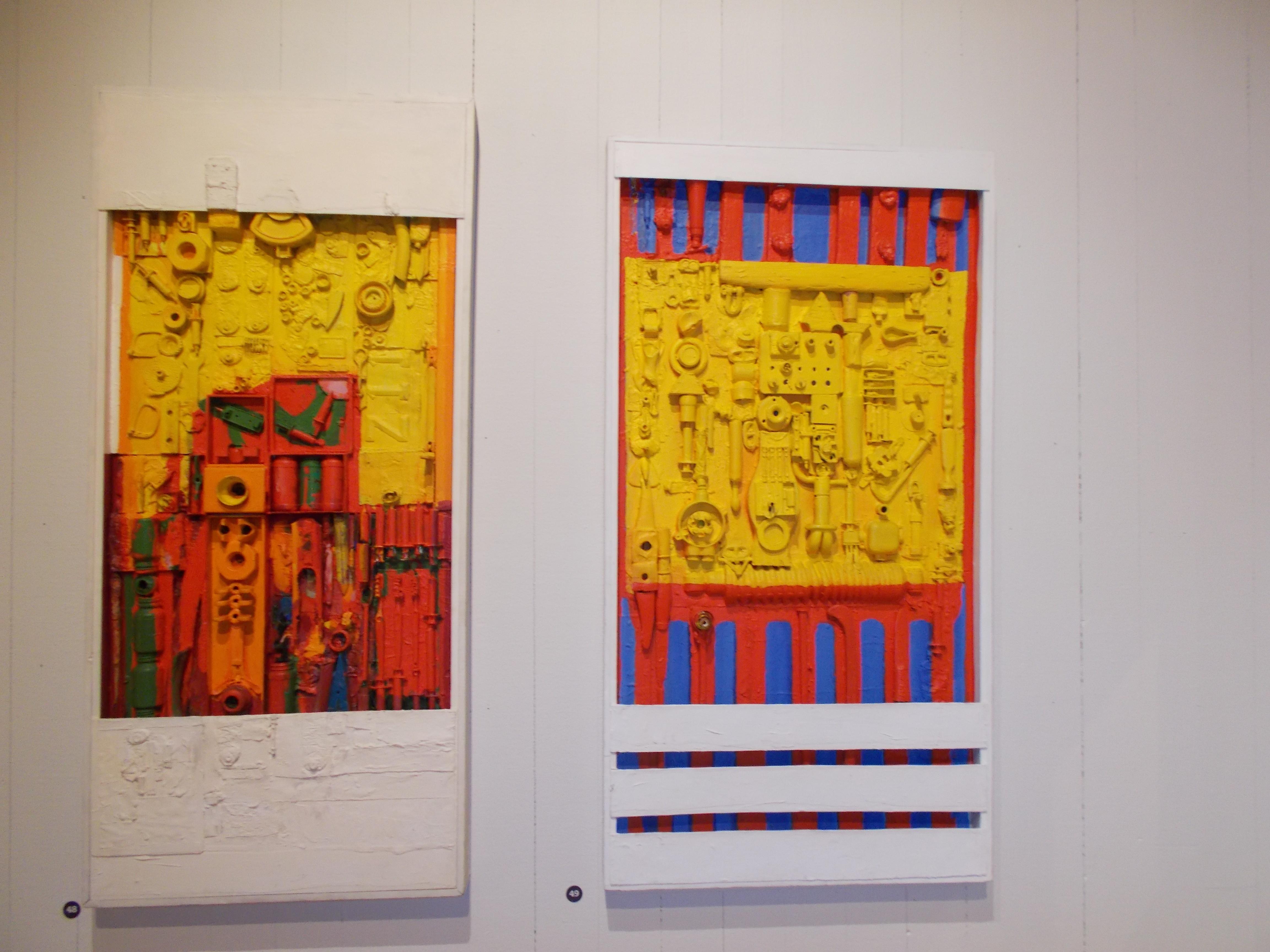 Två färgglada tavlor med mycket rött, gult och gulmålade verktyg.