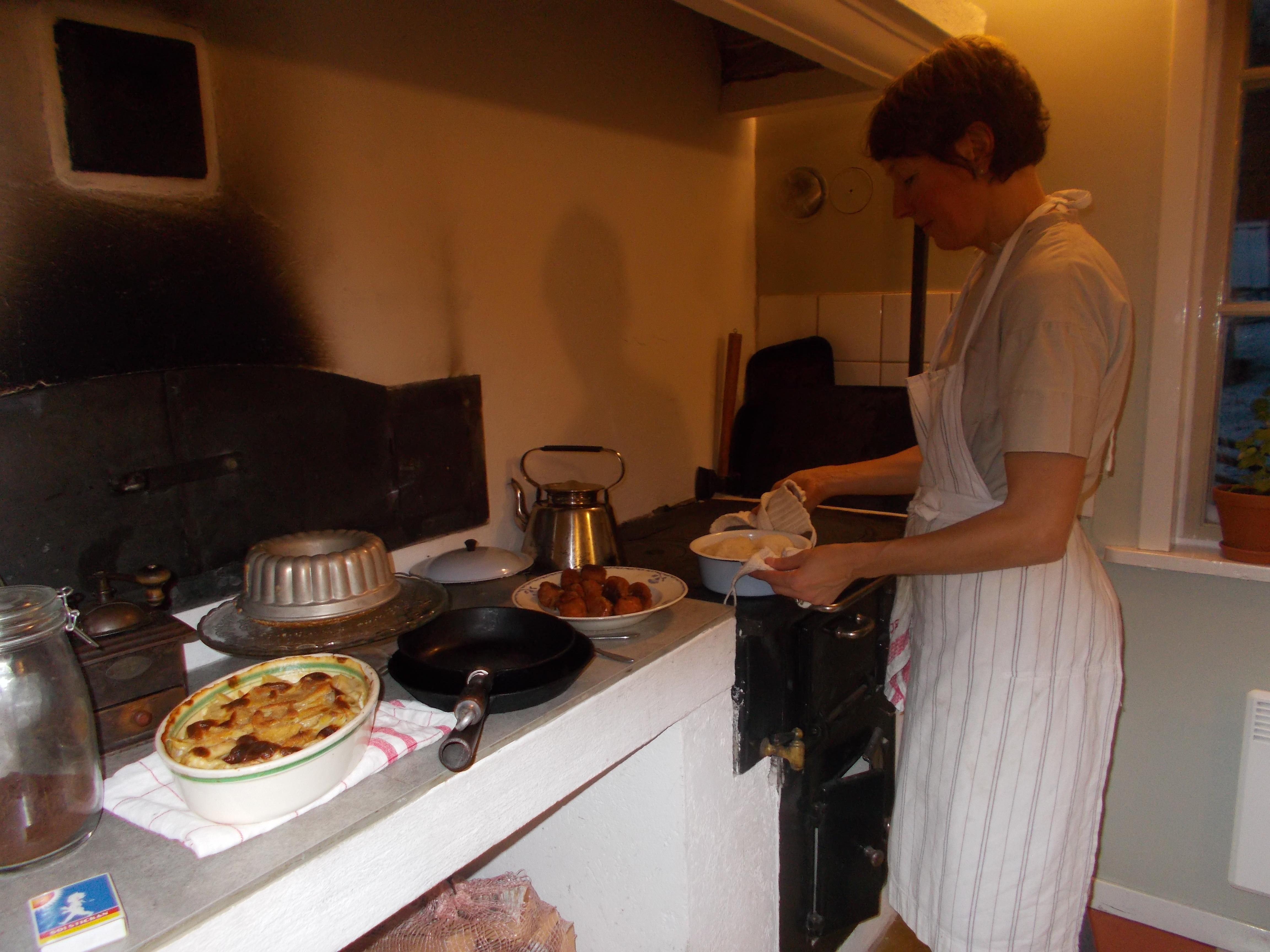Ulrika står vid den svarta järnspisen och lagar mat