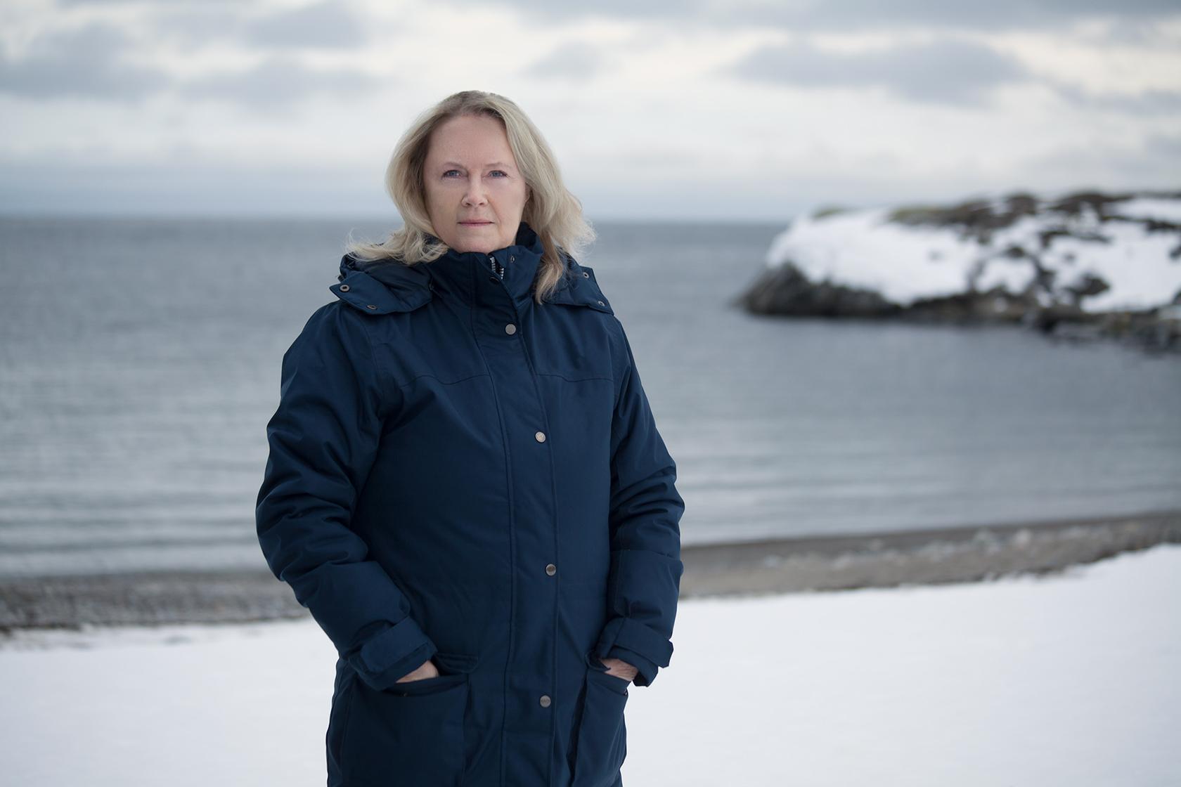 Gittan har blont hår och en blå vinterkappa på sig i ett snörikt vinterlandskap vid havsbandet