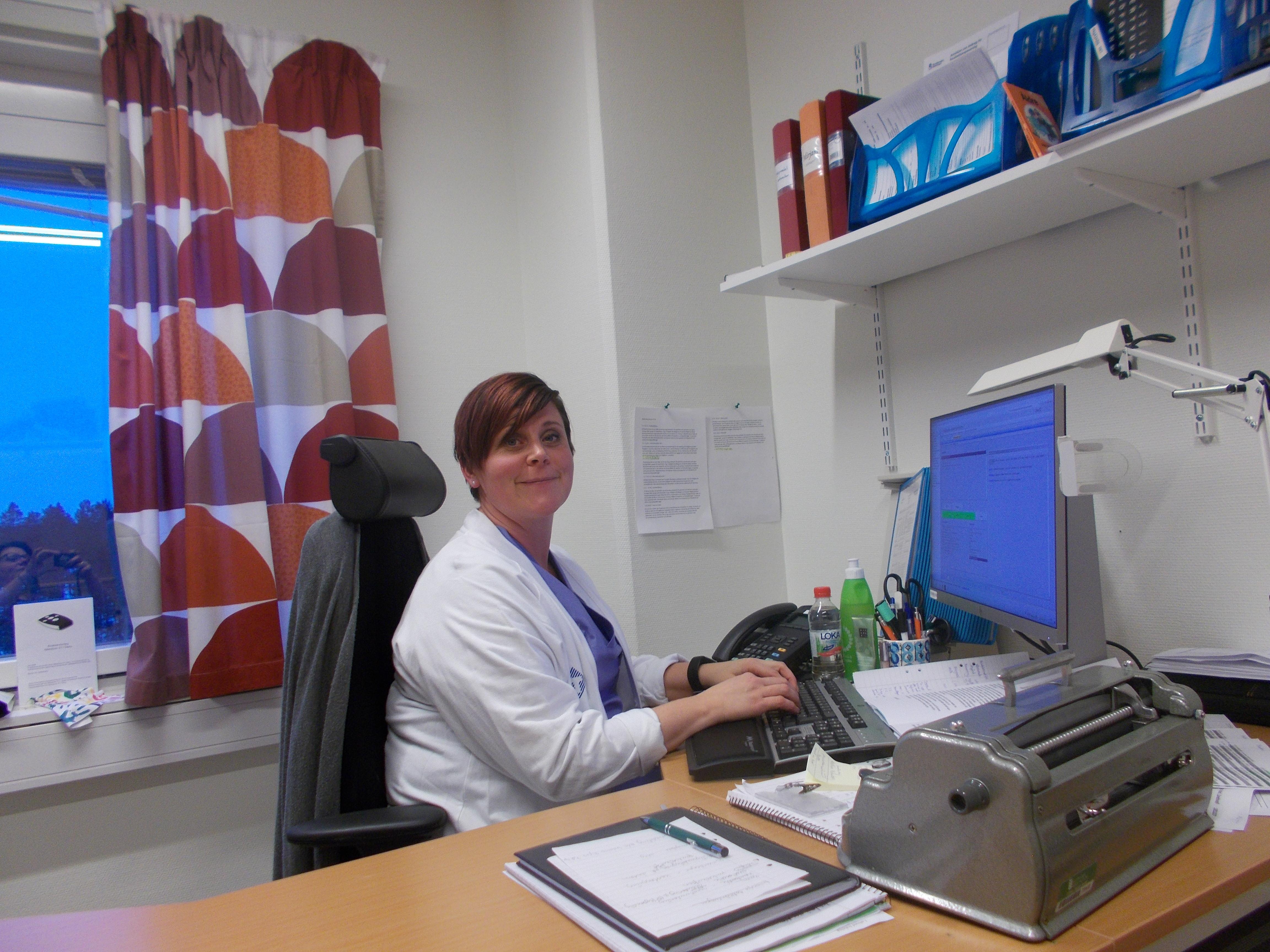 Mirjam sitter vid sin dator och skriver journaler. Hon bär Regionens vita och blå tjänsteuniform.