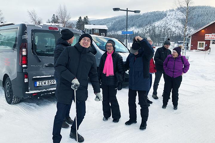 Ett gäng glada, skidklädda personer står vid en snöig parkering i Åre.