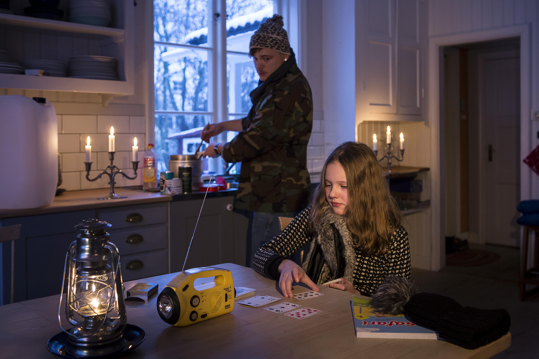 Två ungdomar i ett kök med tända ljus och med en ficklampa på bordet