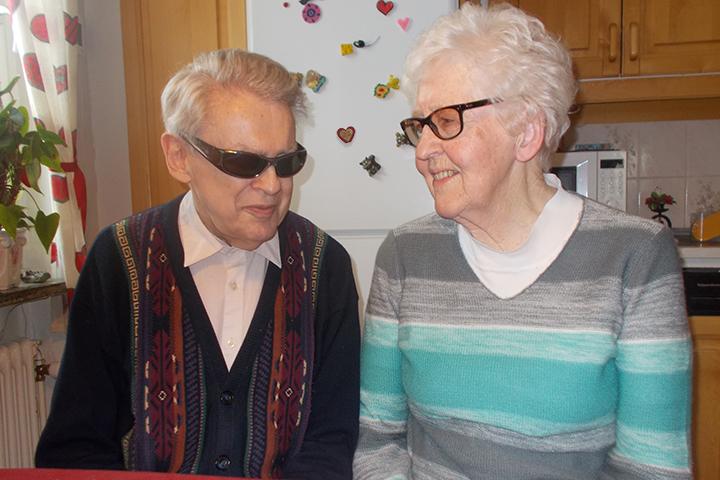 Matts och Anna sitter i köket vända mot varandra och ler kärleksfullt. Ett hjärta på kylskåpet bakom skymtar