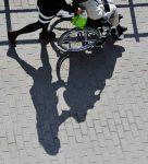 Ben och händer som styr en rullstolsburen framför sig och skuggan av ekipaget i förgrunden