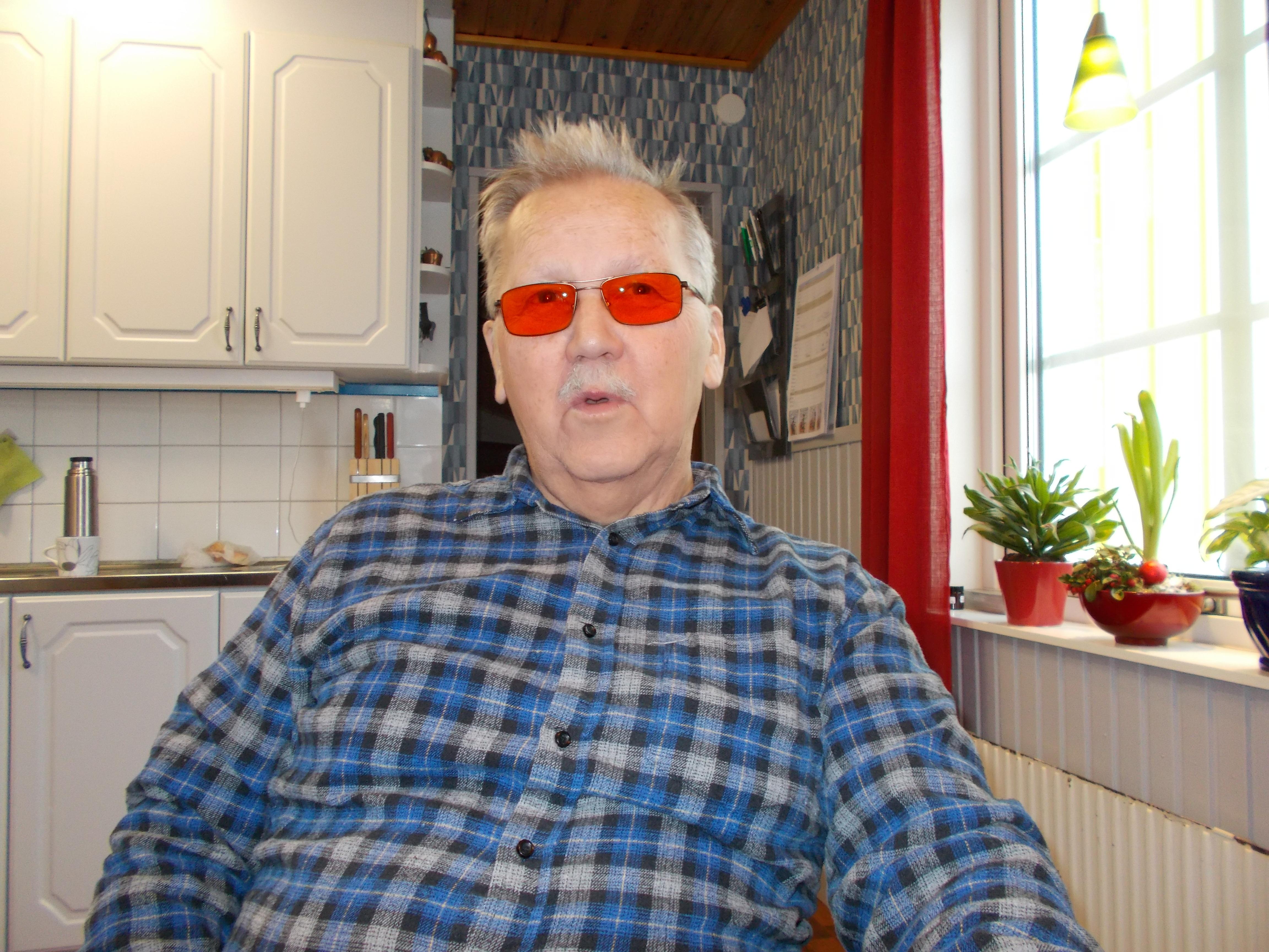 Anders har grått, kortklippt hår och färgade glasögon. Han bär en blårutig skjorta.