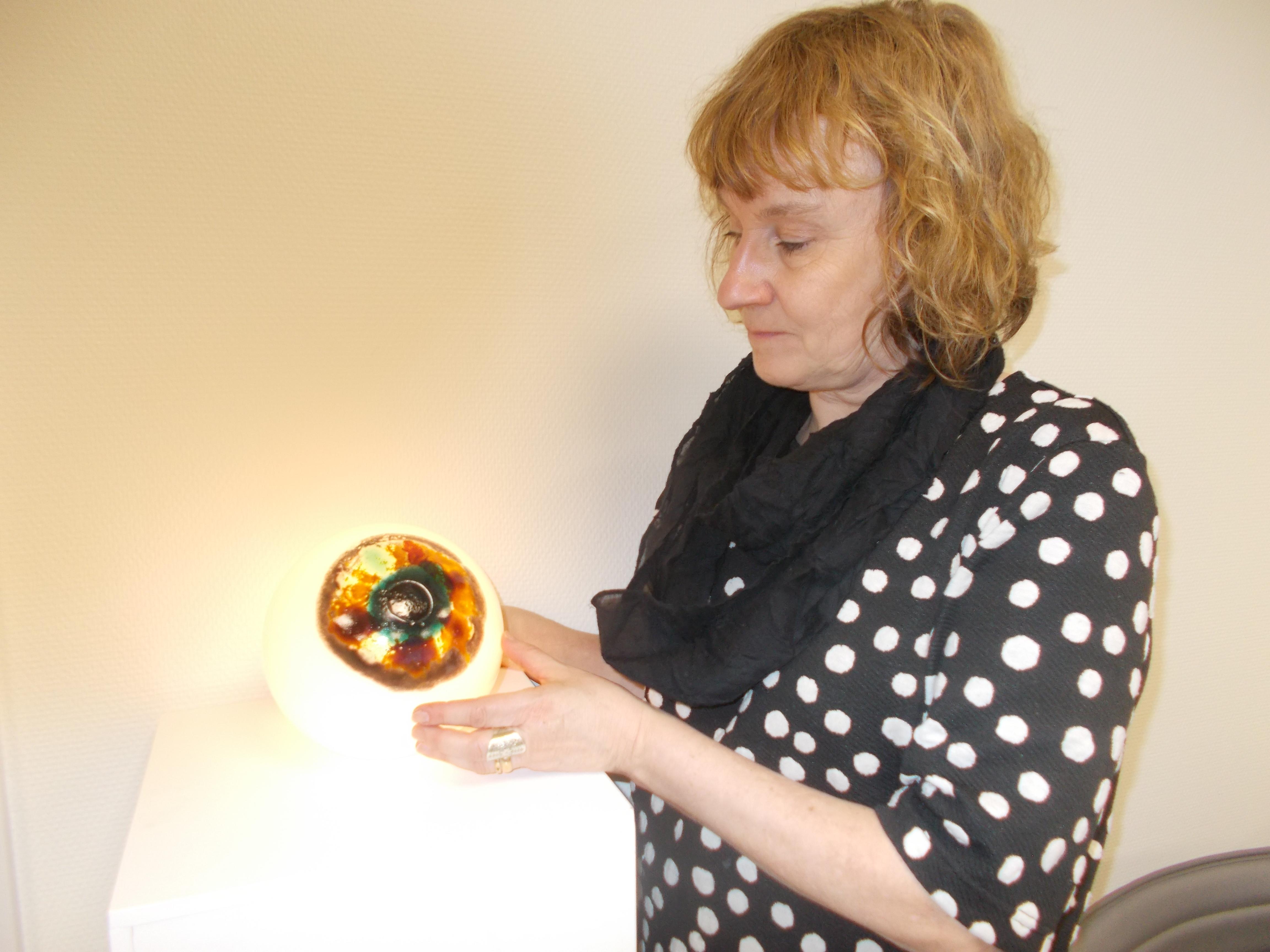 Eva-Leena betraktar konstverket Ögon med sin brunmelerade iris