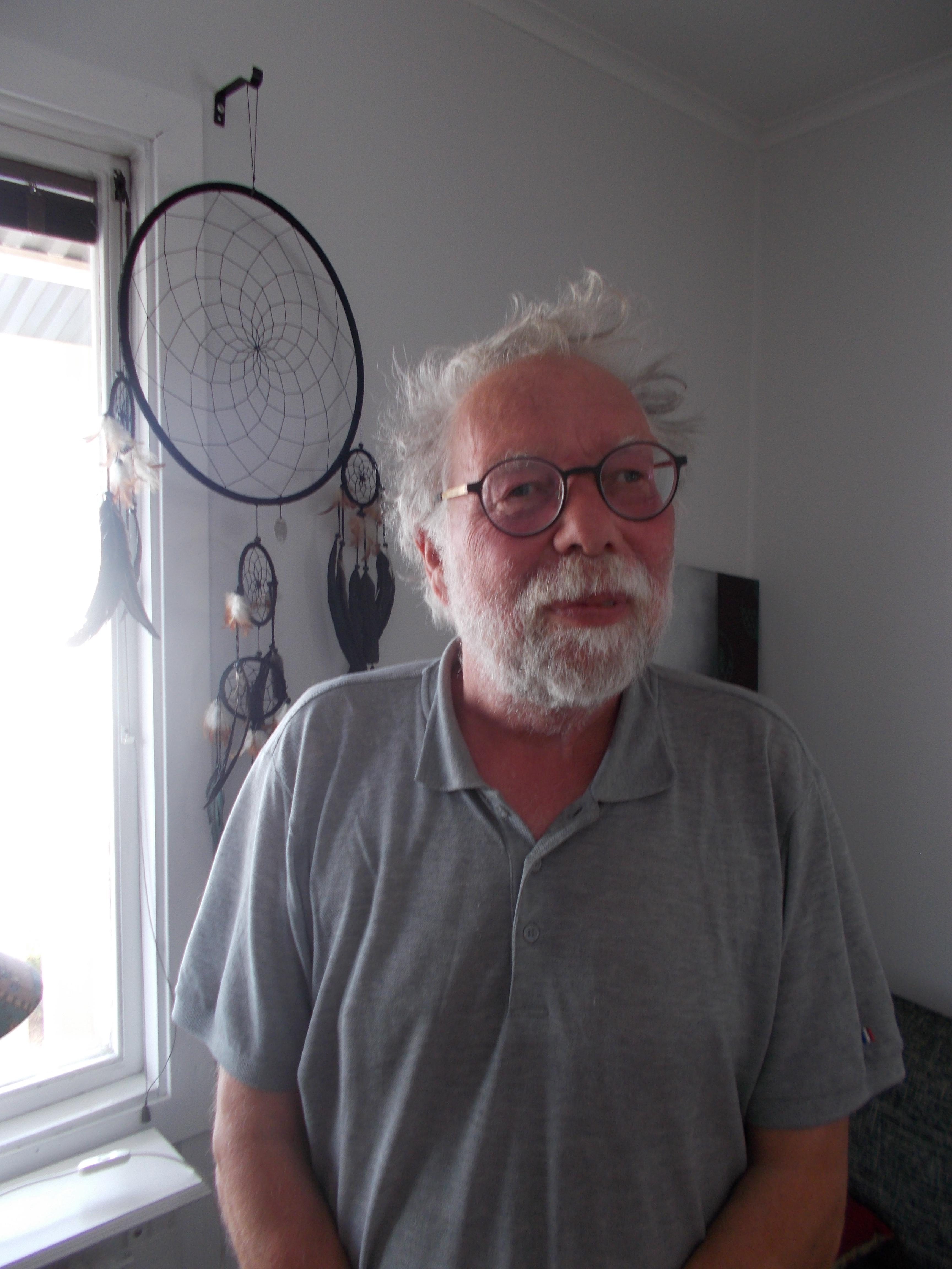 Per-Ingvar har grått, yvigt hår och mörka glasögonbågar