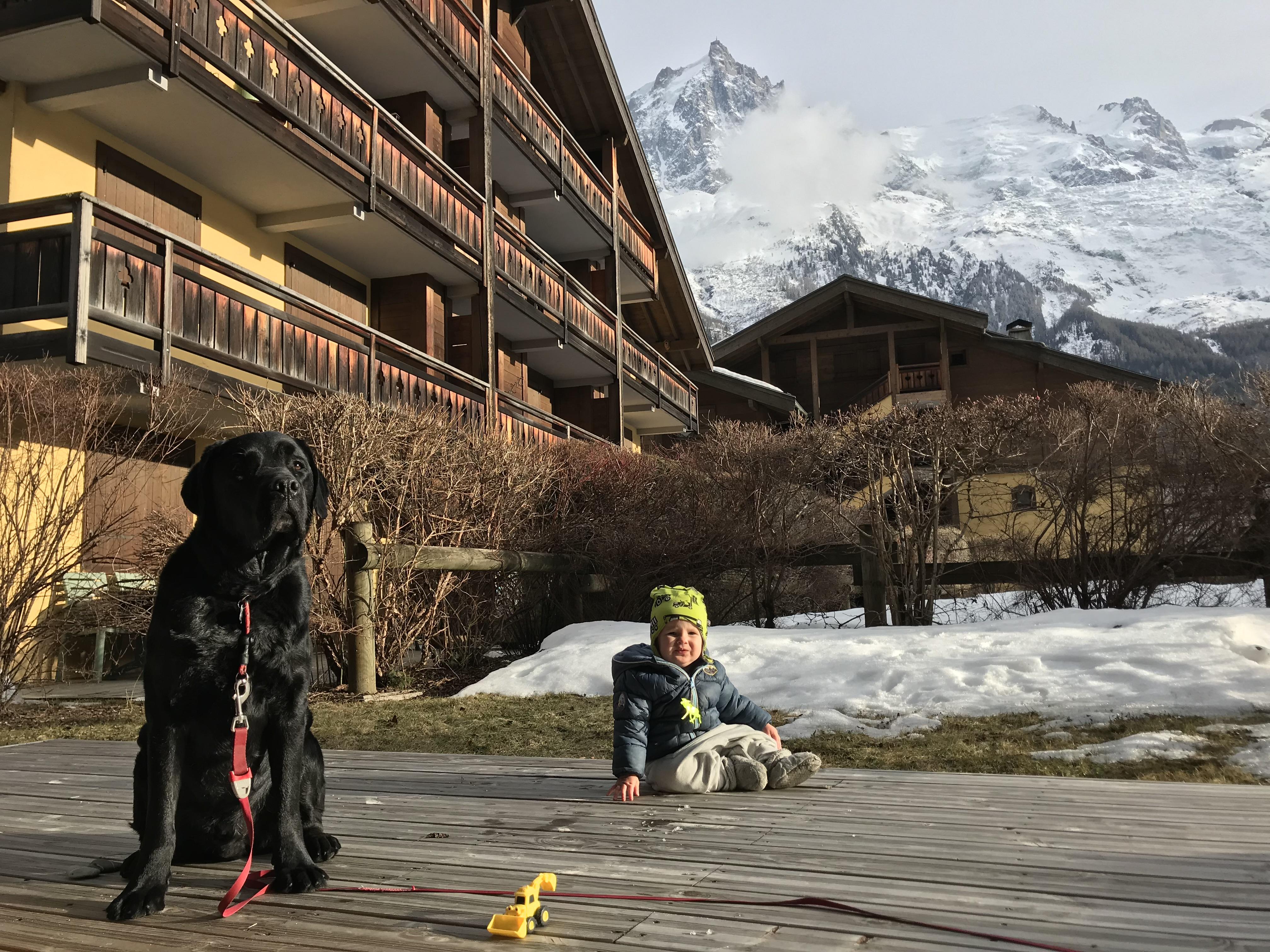 Elliott sitter på uteterassen med hunden Lipton. I bakgrunden de snörika franska alperna