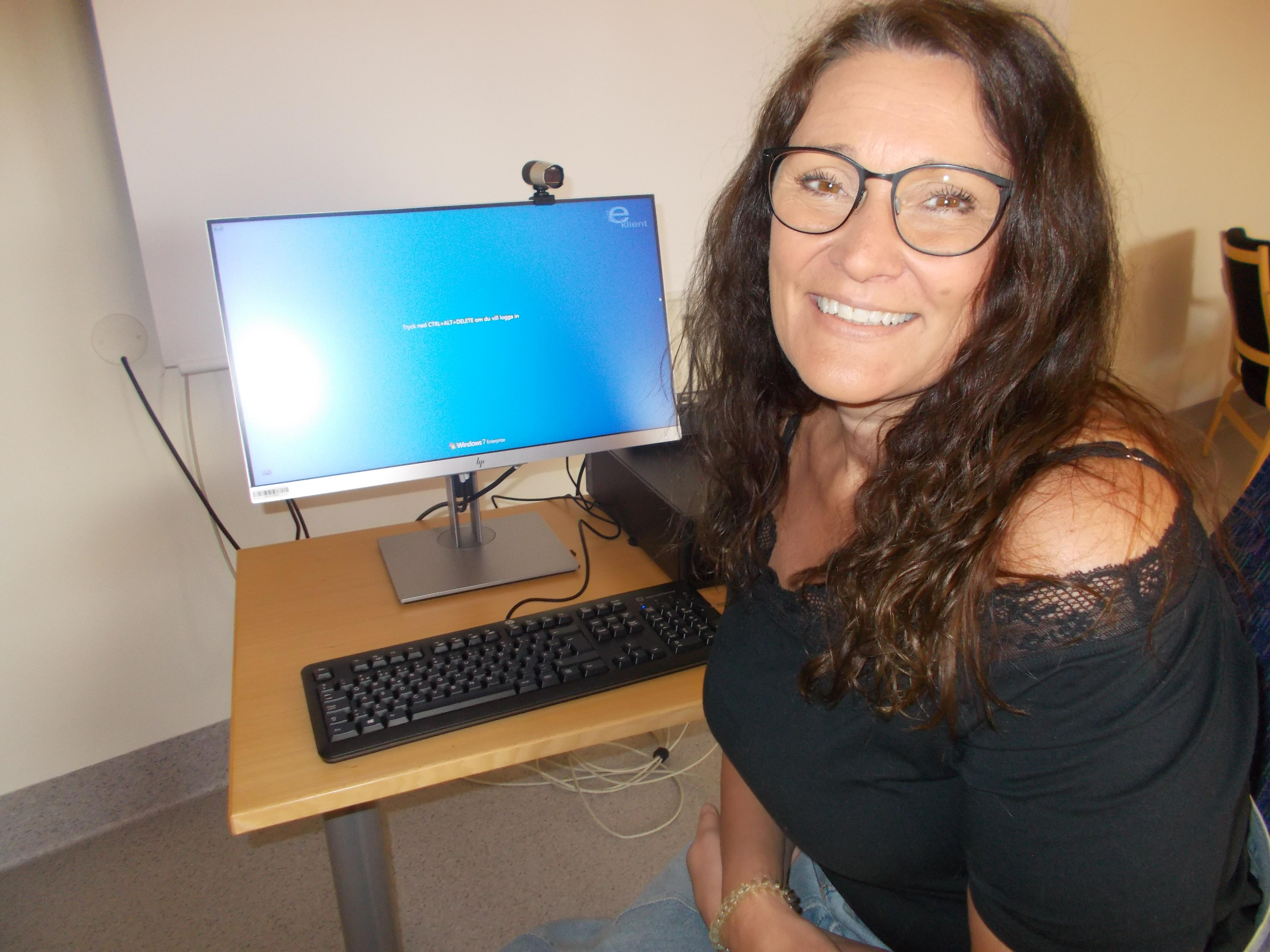 Annika sitter framför en dator. Hon har brunt långt hår och glasögon.