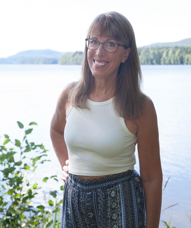 Pia har långt hår och glasögon. Hon bär en vit topp och blå mönstrade byxor.