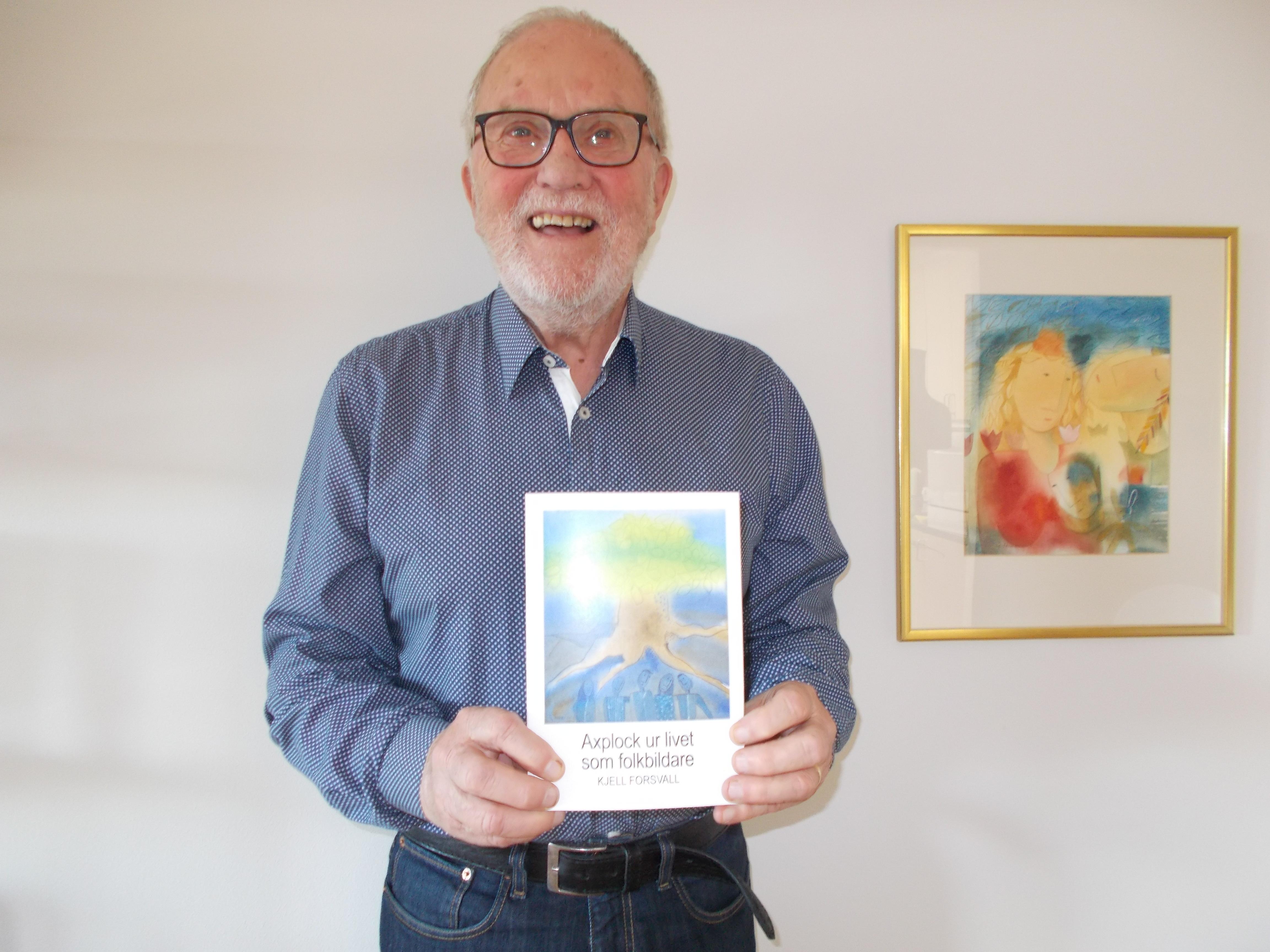 Kjell har glasögon och grått skägg. Han bär en blå skjorta och håller i sin nya bok framför sig