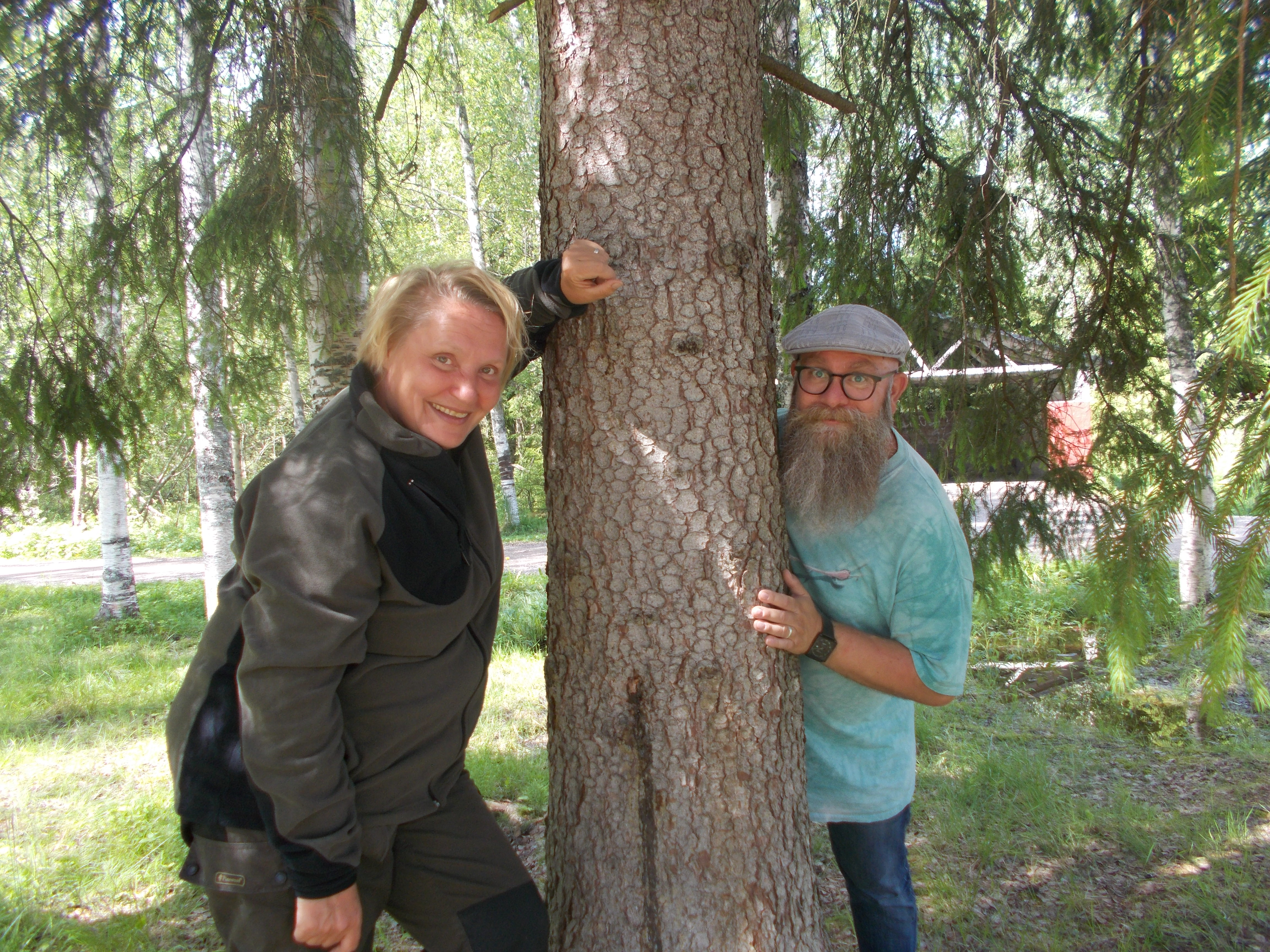 Ulla och Fredrik står bredvid en tall i en skog