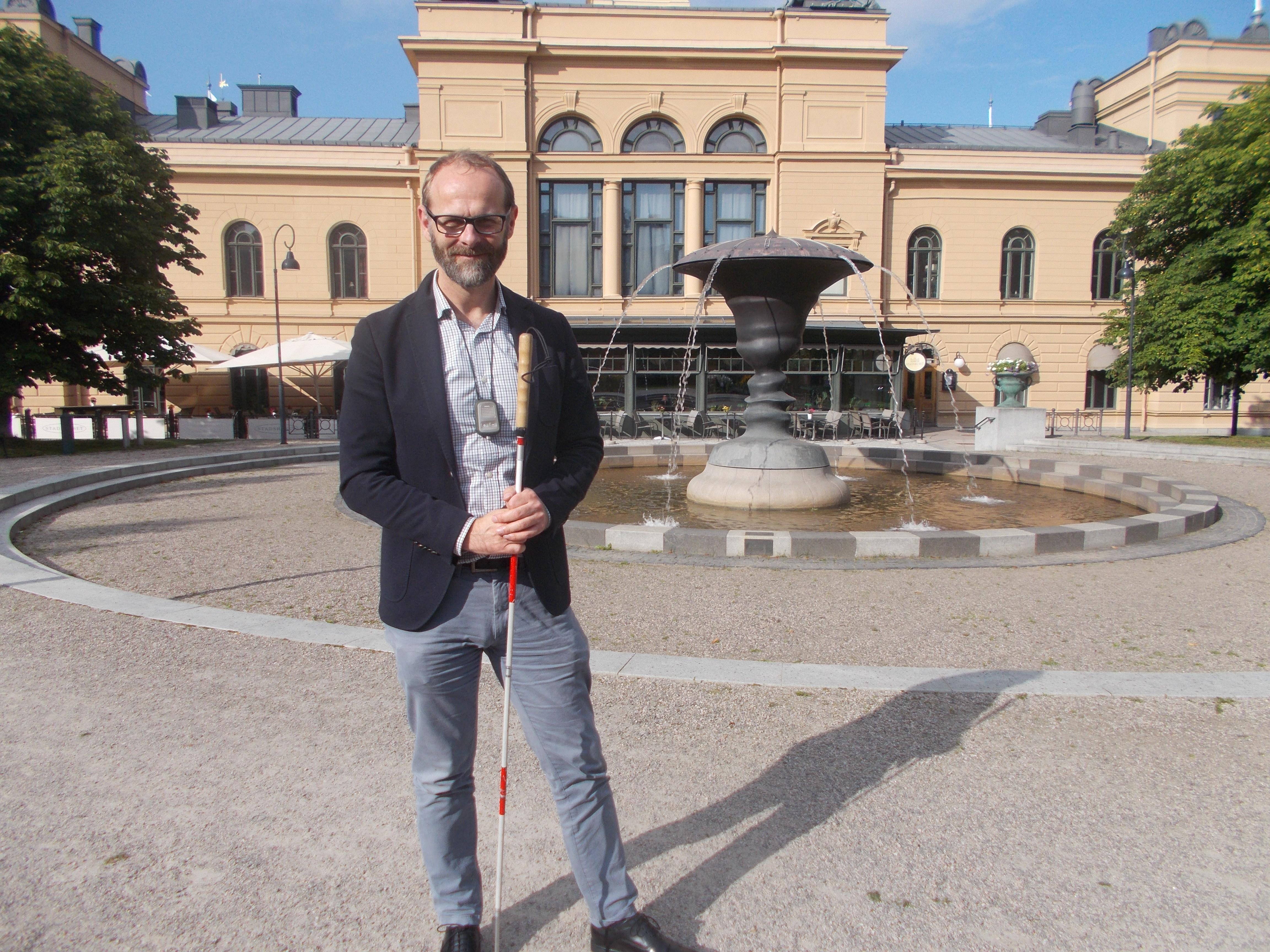 Klas står vid fontänen vid Sundsvalls Stadshus. Han har den vita käppen med röda markeringar i ena handen.