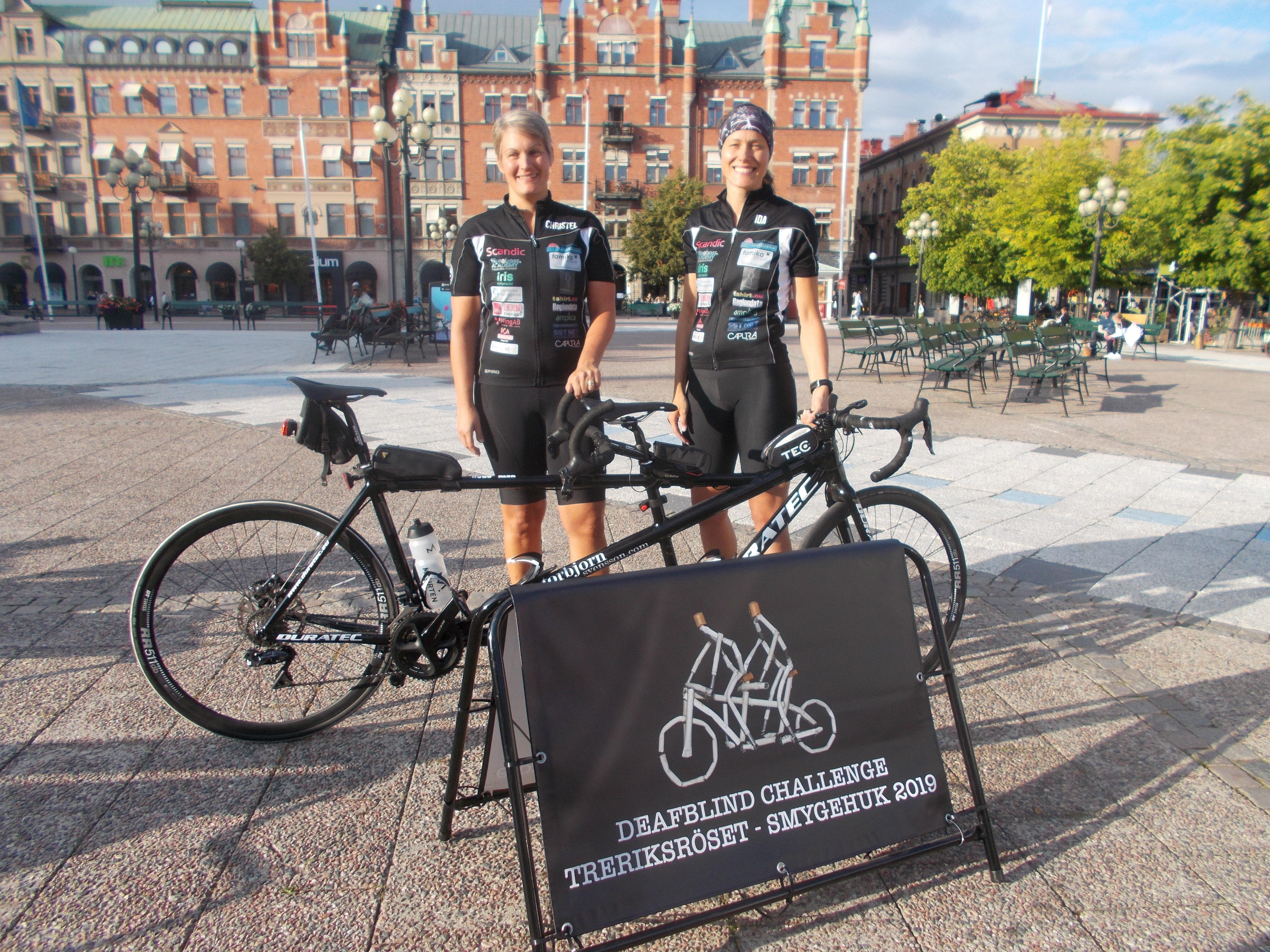 Christel och Ida iklädda tajta cykeldräkter bakom den svarta tandemcykeln på Stora torget i Sundsvall