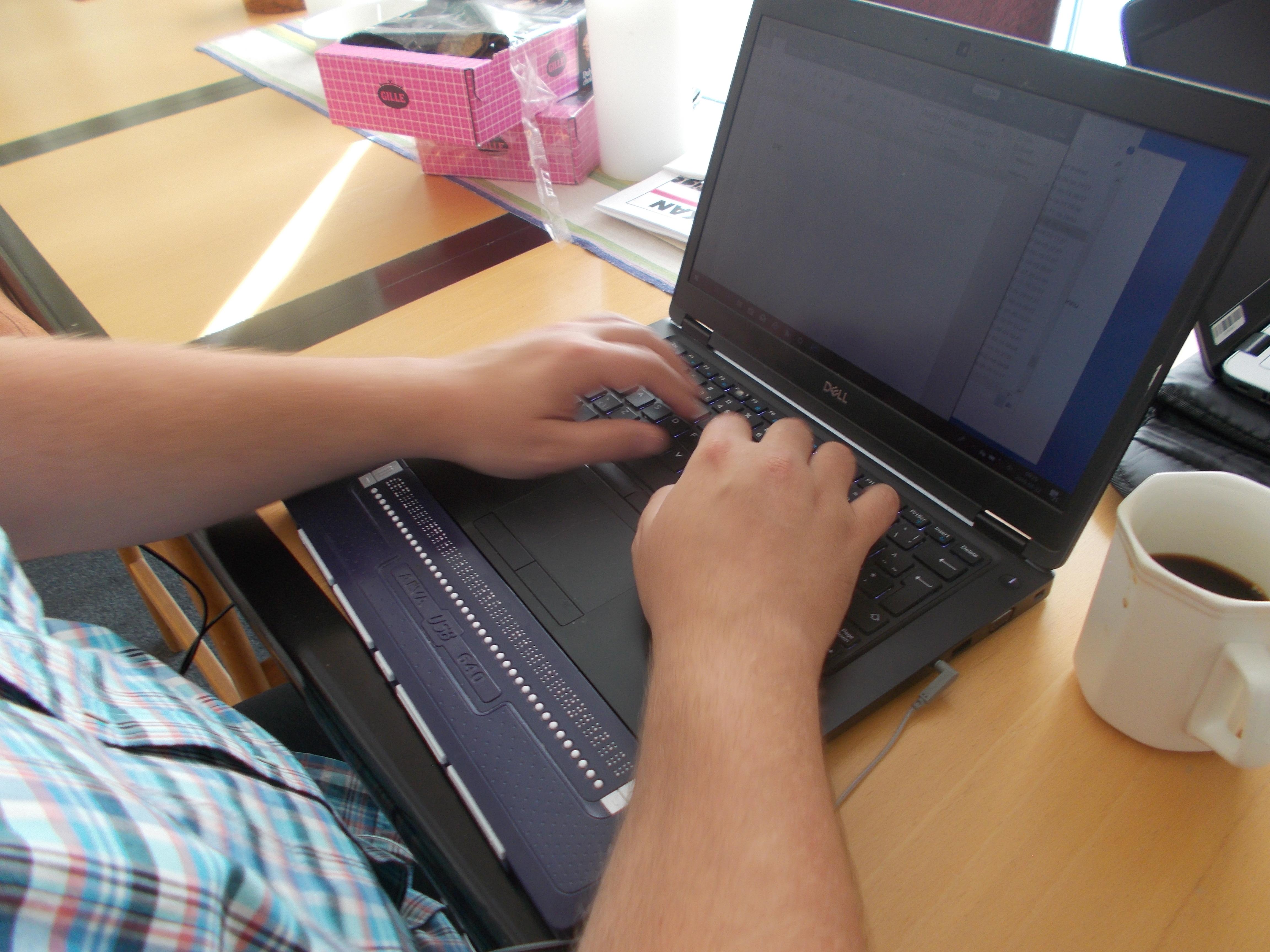 Skrivande händer i närbild på en dator med punktdisplay och tangentbord