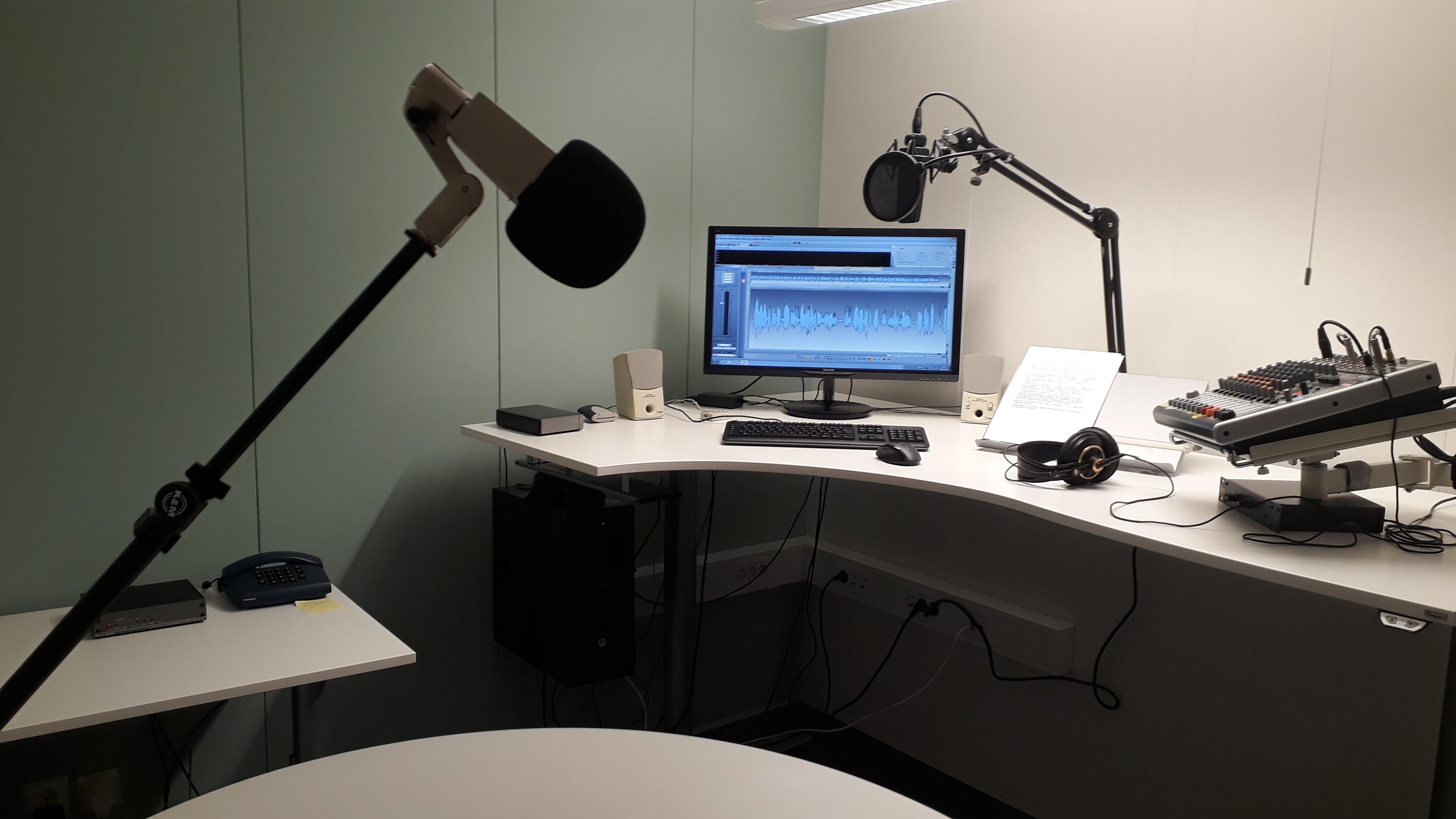 Grön fondvägg i ljudstudion och inspelningsutrustning på det vita skrivbordet