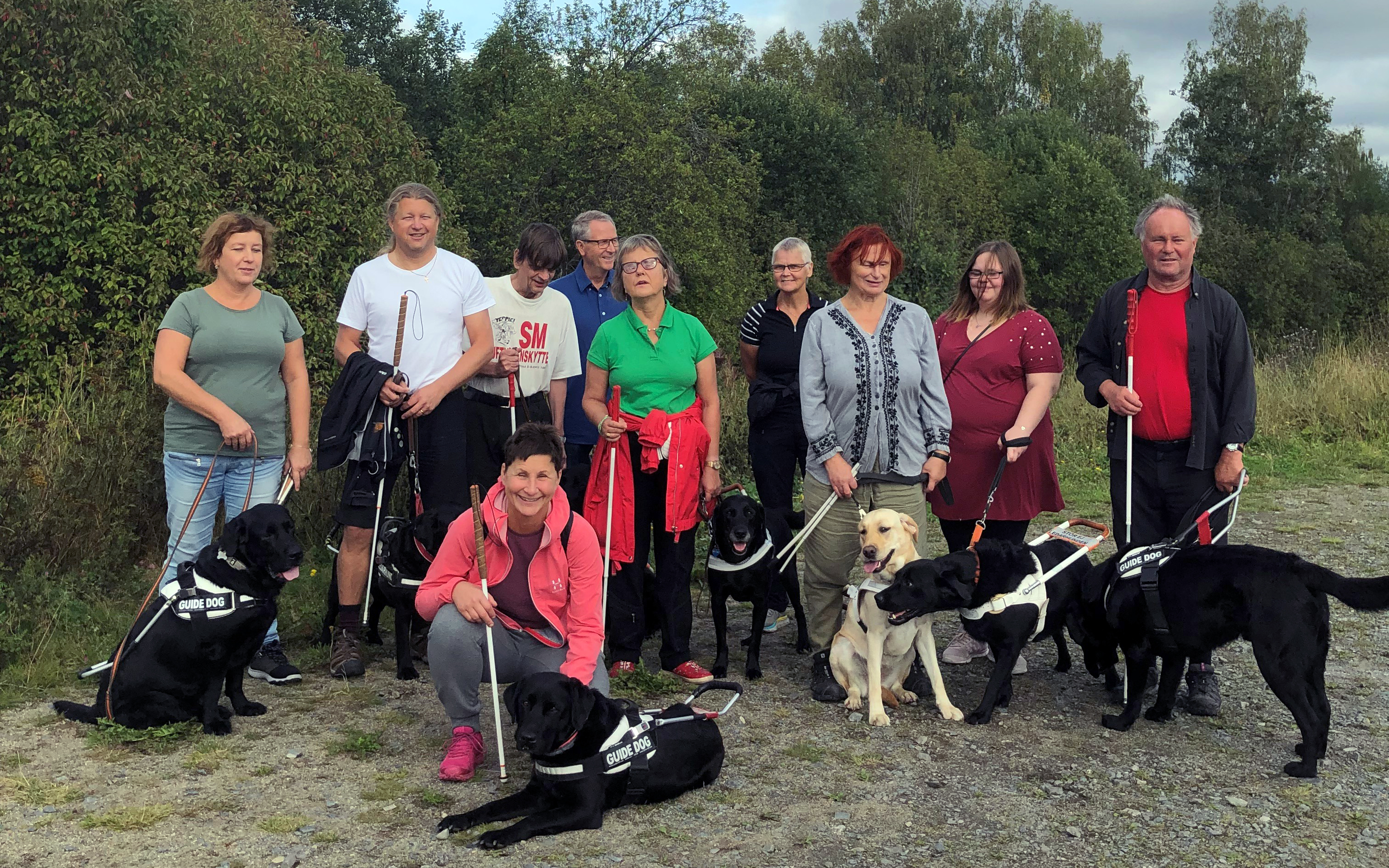 Tio personer, kvinnor och män, står med sina ledarhundar, alla labradorer.