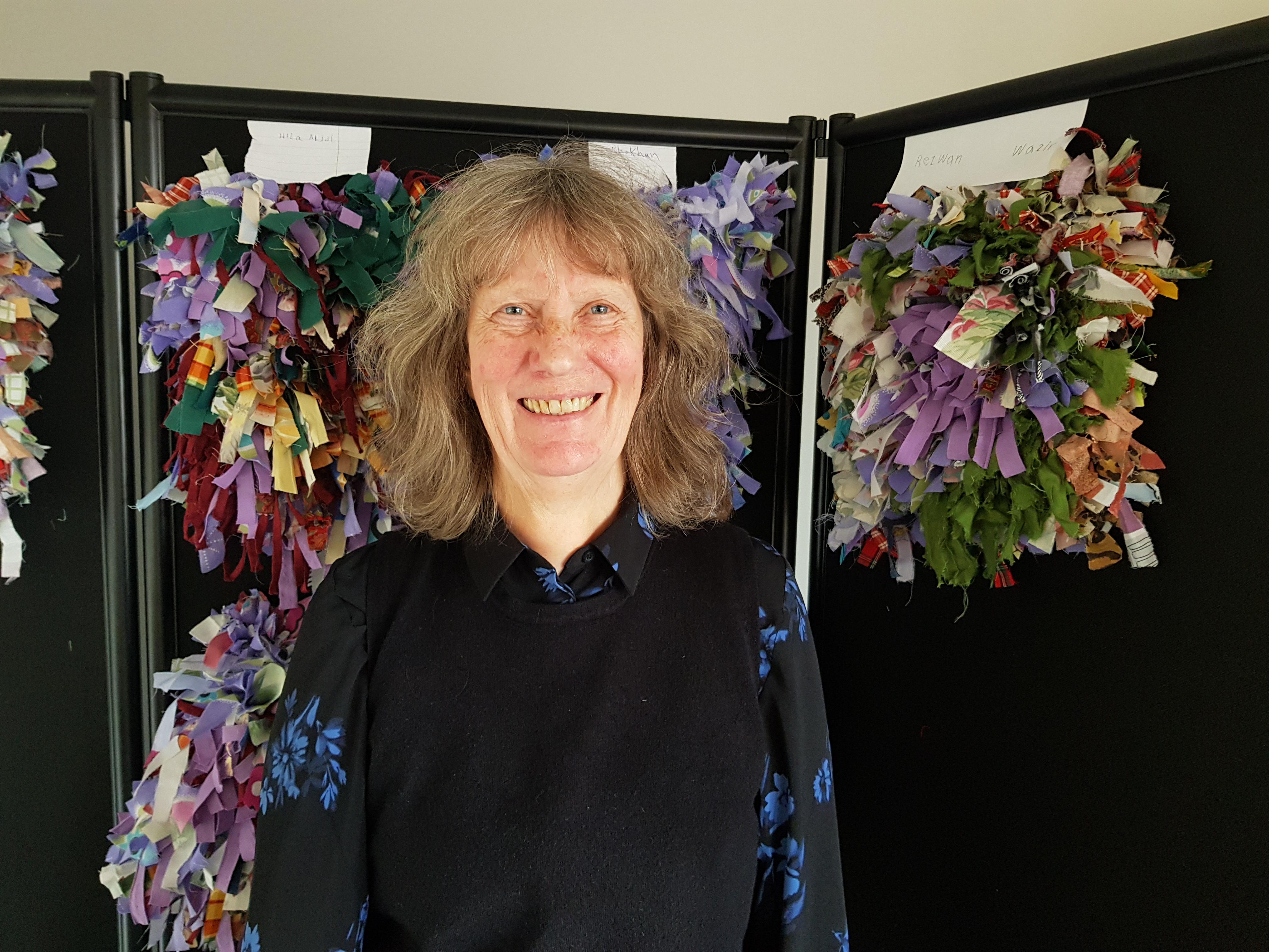 Berit ler och bakom sig har hon elevernas konstverk i olika färger
