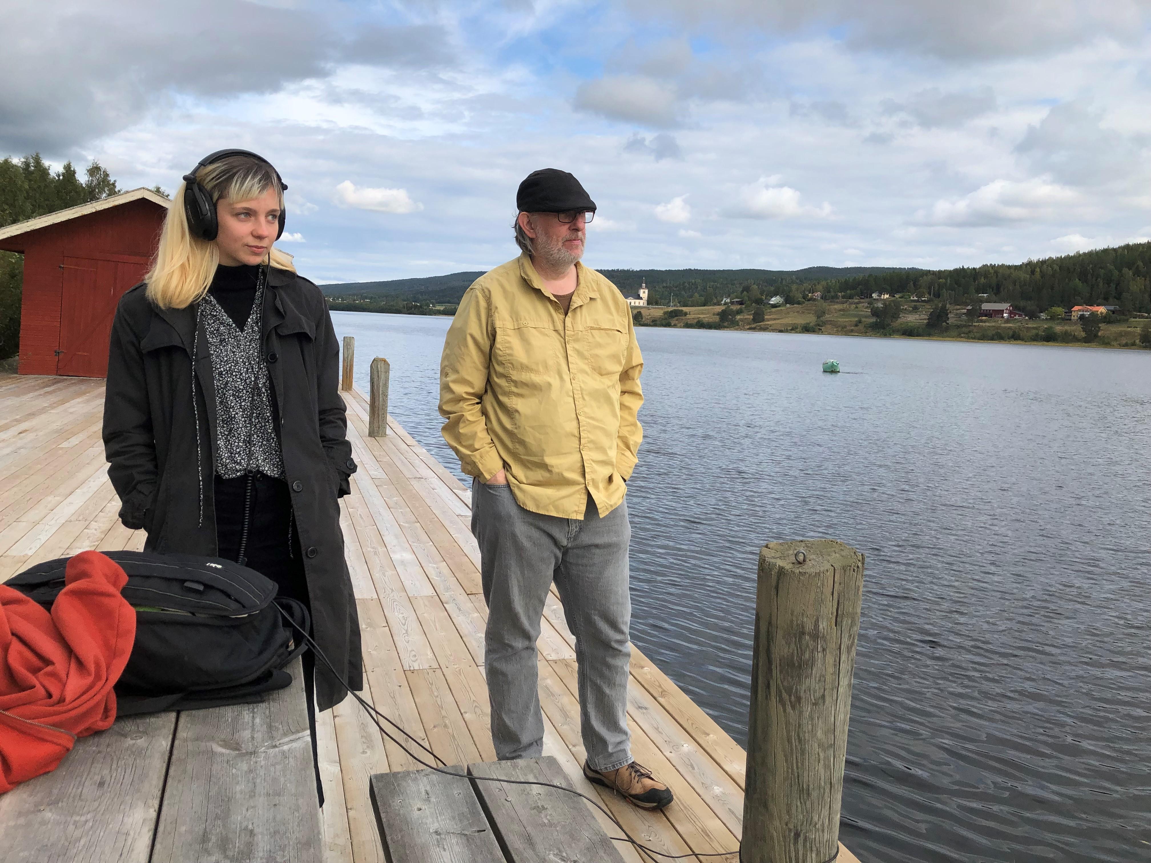 En blond 22-årig kvinna står vid Ångermanälven i kappa och stora hörlurar på huvudet. Hon lyssnar ner i älven. Vid sidan om henne står en 55-årig man, grått hår, keps, skjorta, händerna i byxrfickorna.