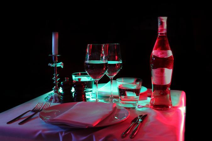 En uppdukat bord med tallrikar,servetter, vinflaska och vinglass i skymningsmörker