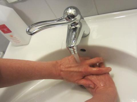 Någon tvättar sina händer i en vitt handfat med rinnande vatten