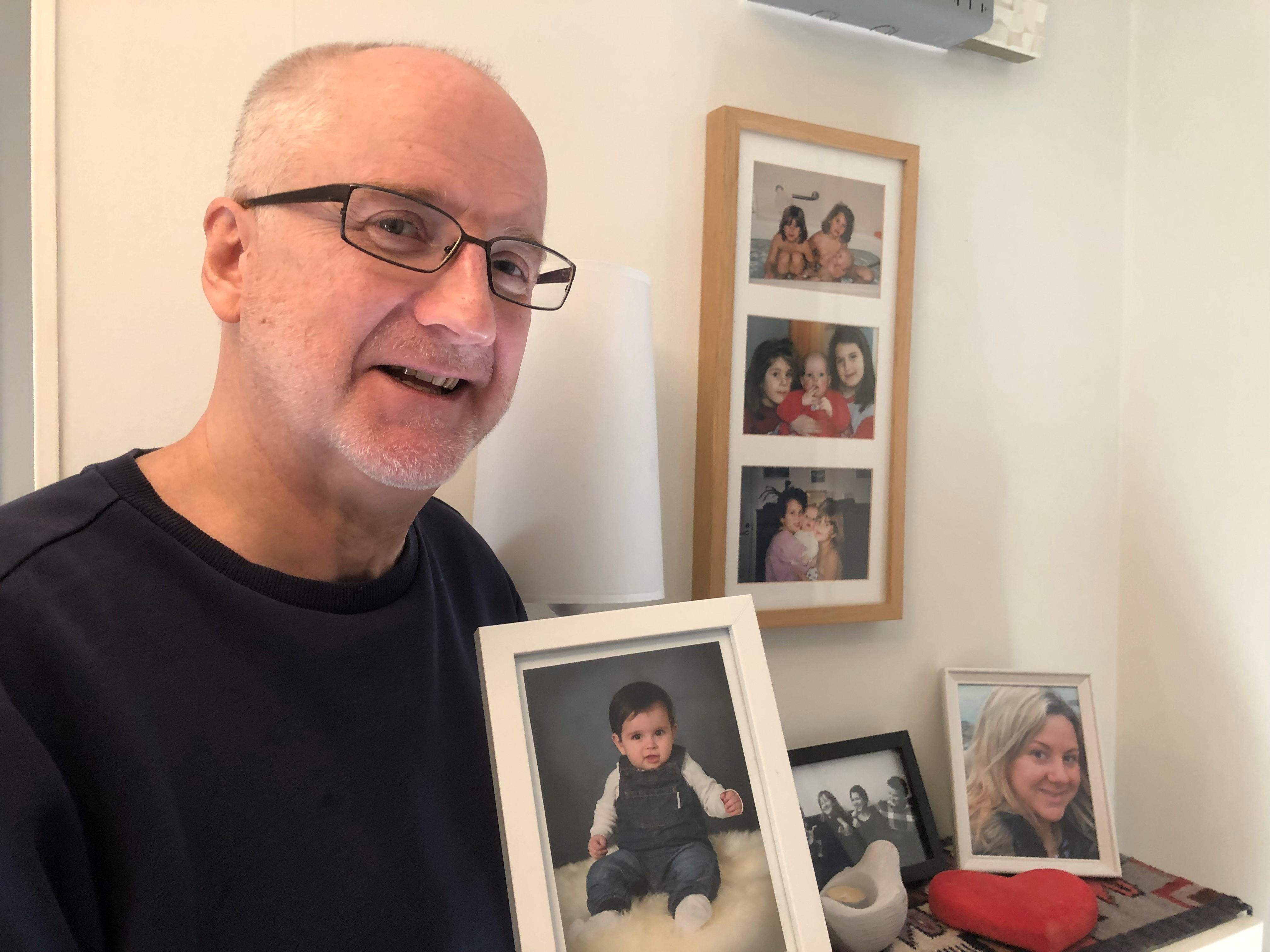 Kjell-Åke har grått snaggat hår och glasögon. Han håller i ett porträtt på sitt barnbarn och ler stolt.. På väggen bakom hänger flera porträtt på hans familjemedlemmar.