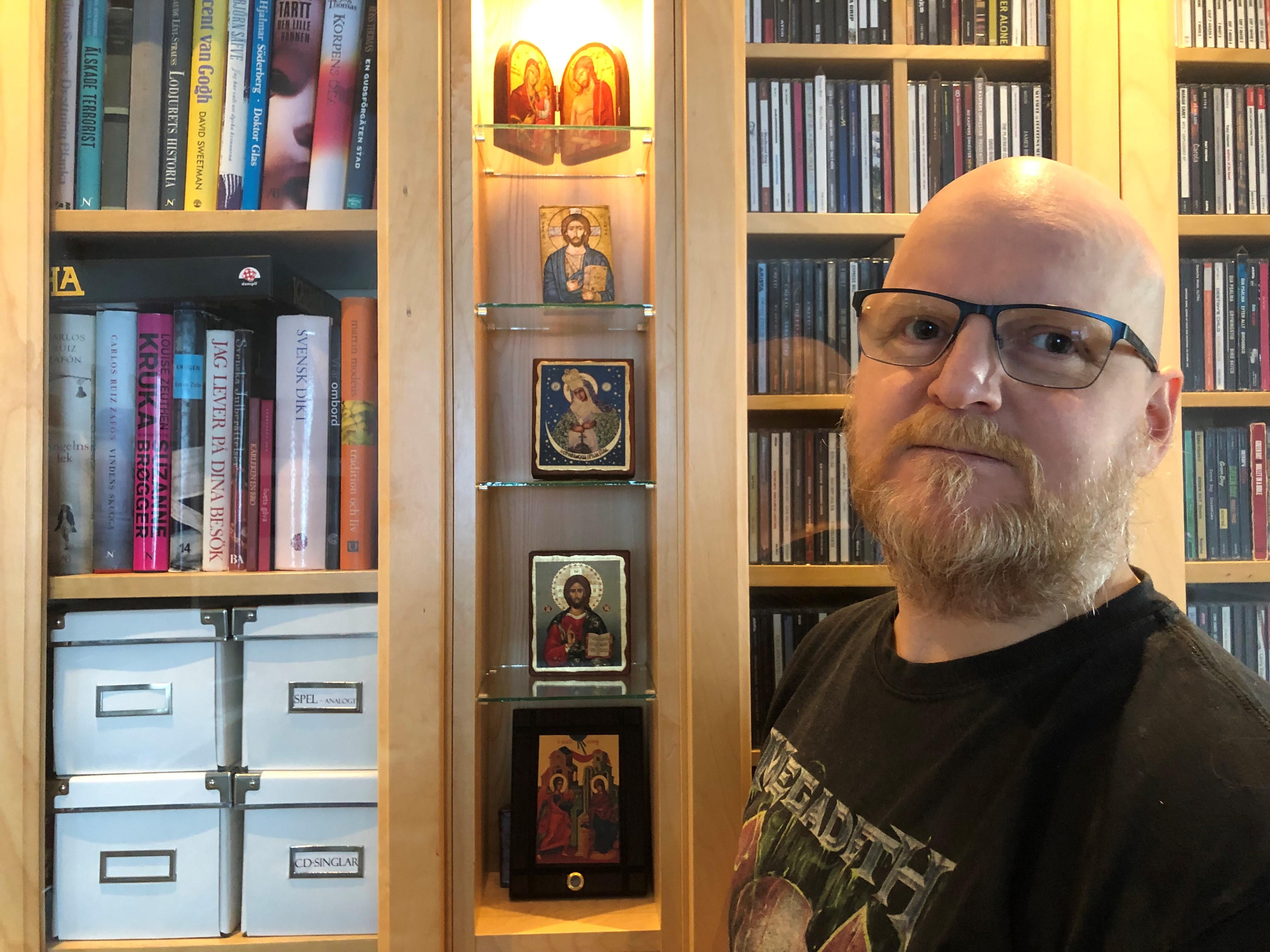 Kenneth har rakat hår och glasögon. Han bär en svart t-shirt. Han står framför sin bokhylla med foton på Jesus