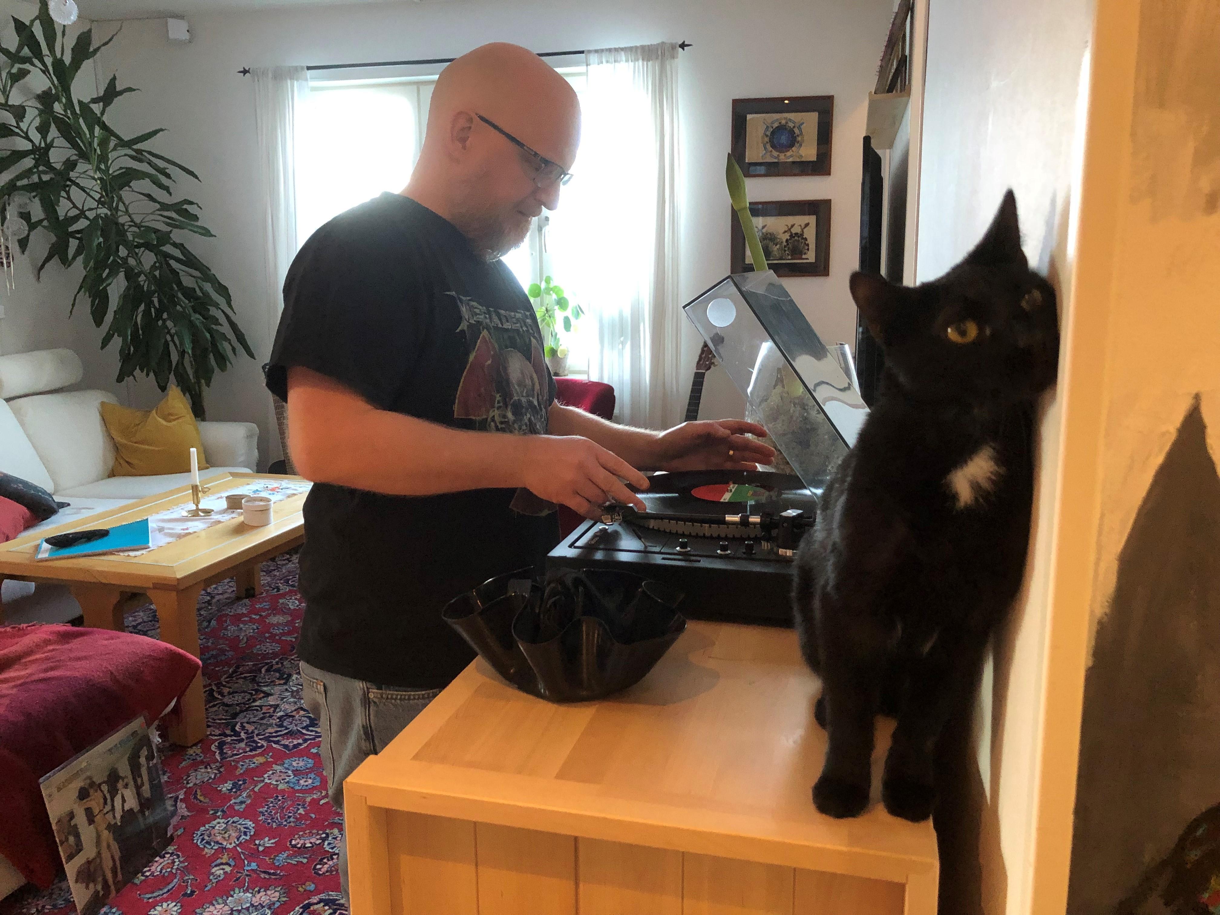 Kenneth laddar en vinylskriva i sin skrivspelare och den svarta katten står bredvid på steriobänken