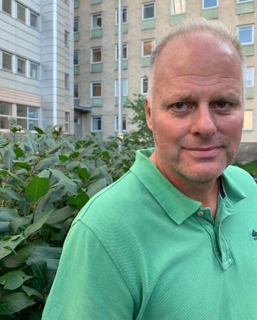 Lars Nyberg har grått hår och högt hårfäste. Han bär en knallgrön tenniströja med knäppning