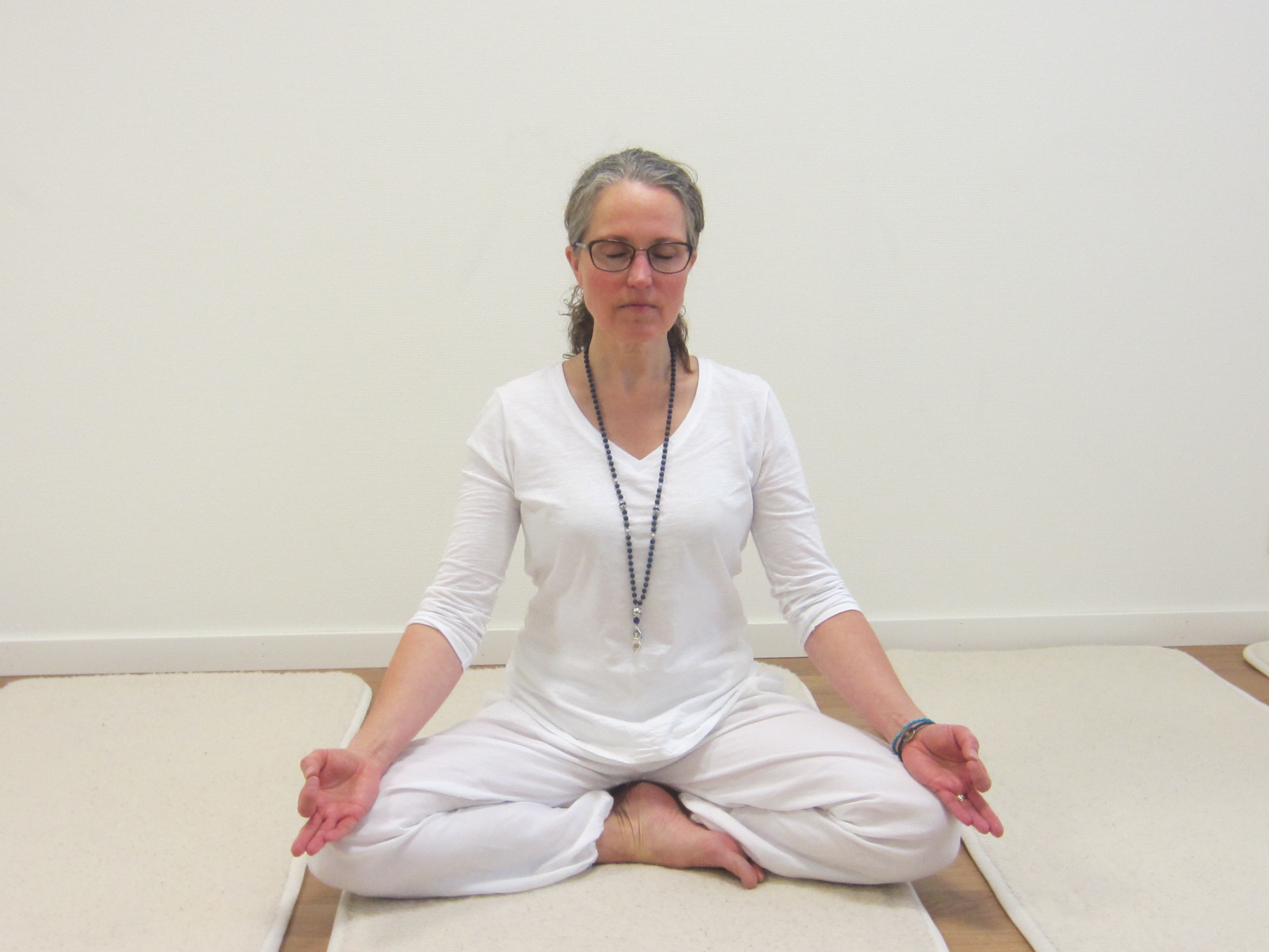 En blond kvinna med glasögon och vit yogadräkt sitter i lotusställning på en madrass