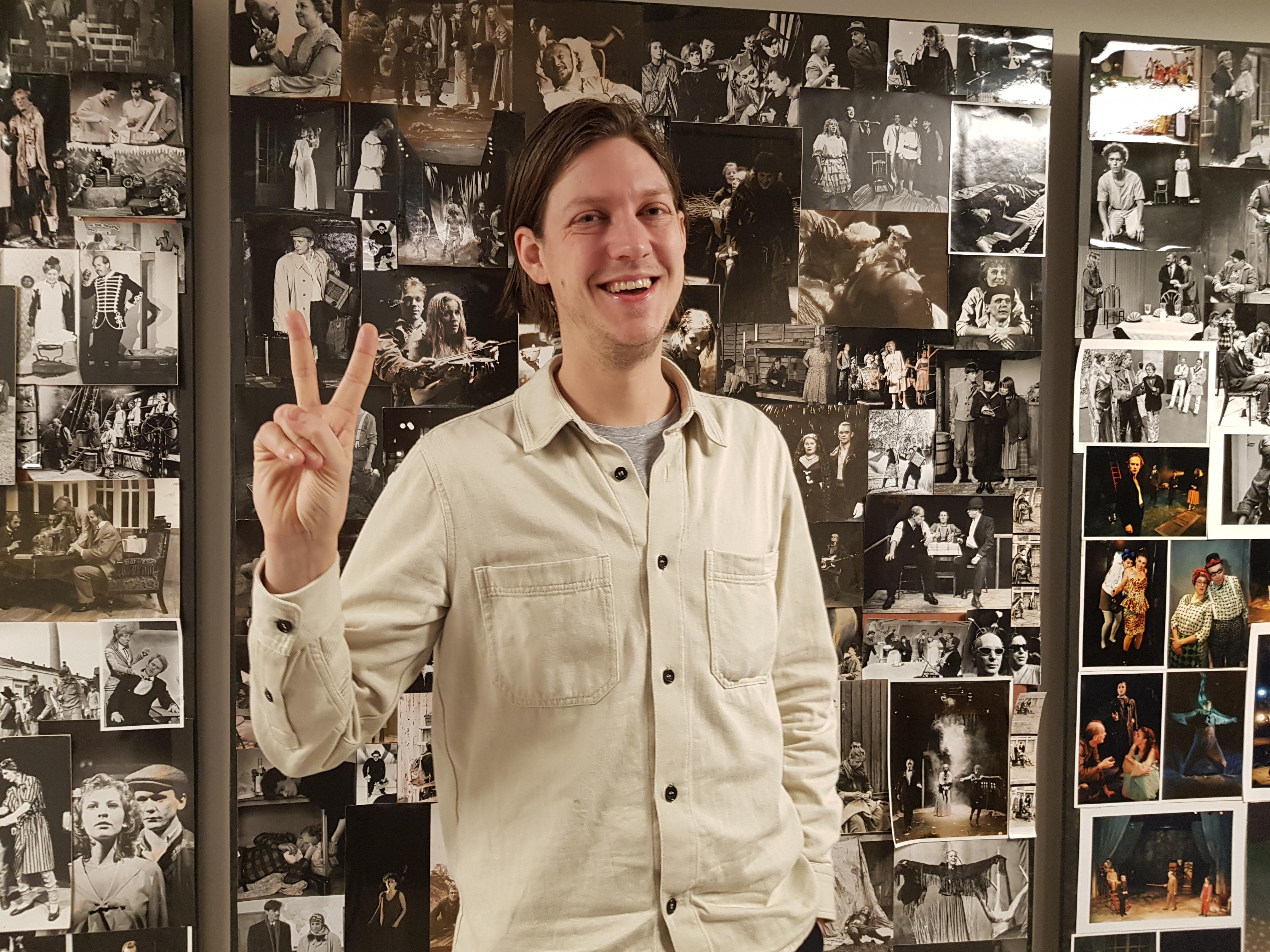 Kristoffer står framför en vägg med svartvita teaterbilder. Han bär en beige jeansskjorta och gör segertecken med ena handen