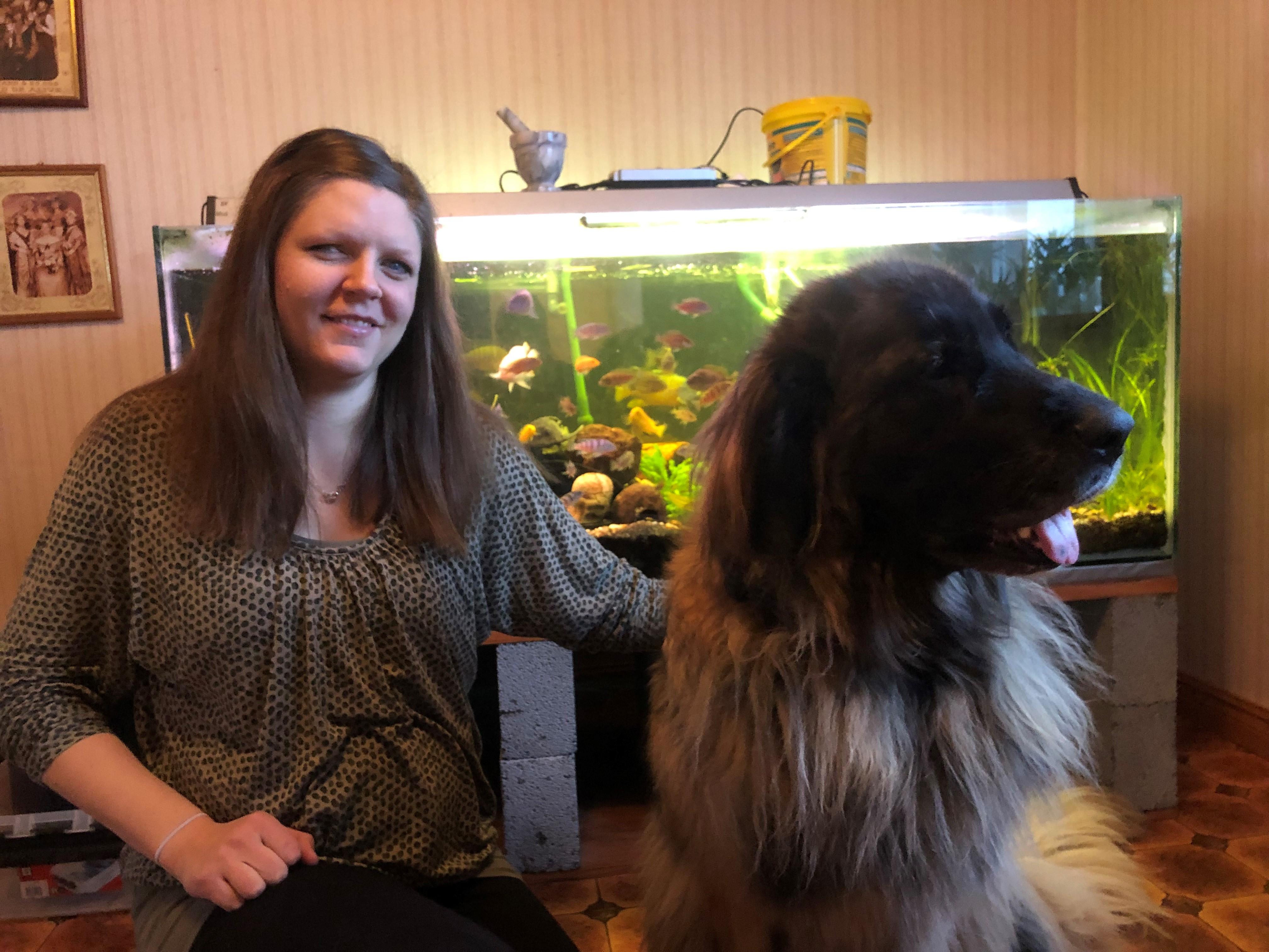 Lisa har mörkt långt hår. Hon sitter framför ett akvarium tillsammans med sin hund Birka