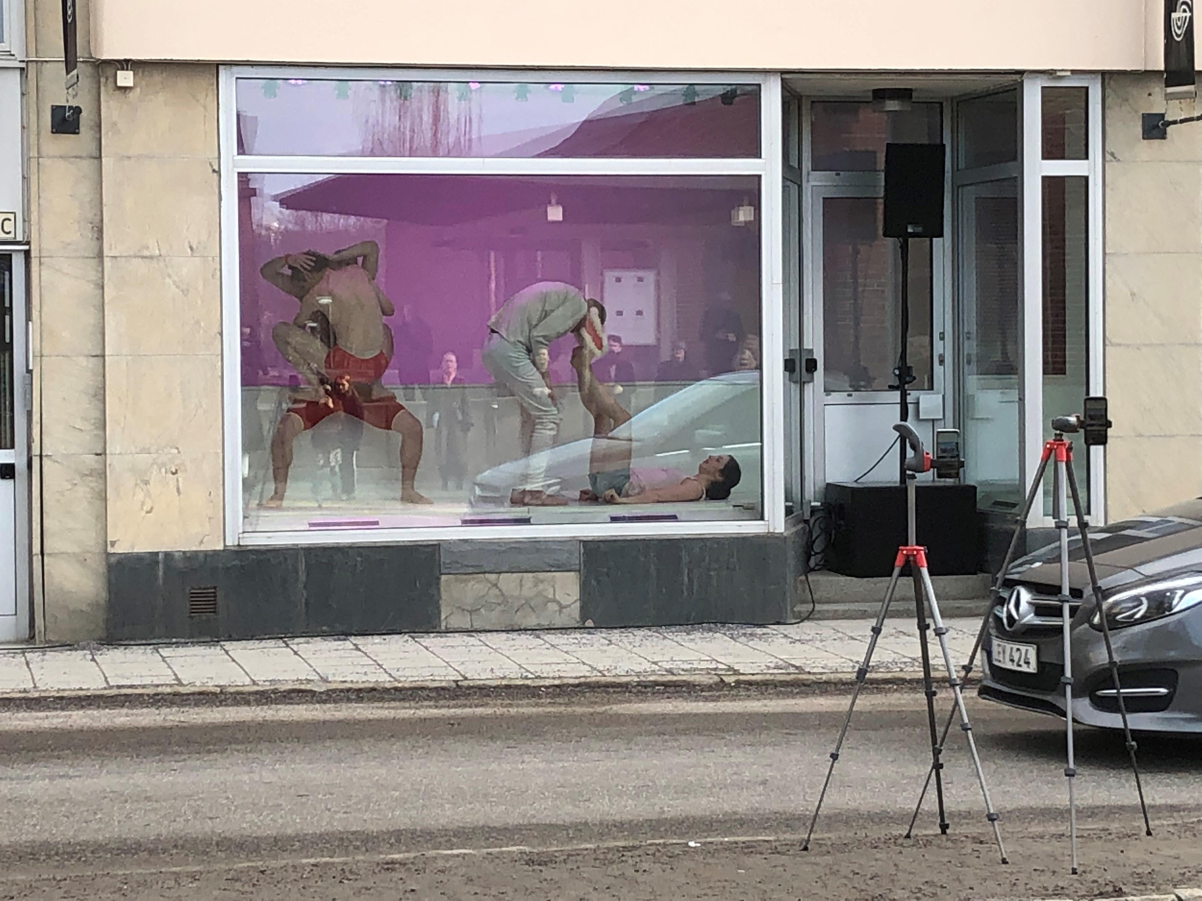 Dansare i ett skyltfönster i Härnösand. Framför skyltfönstret kör bilarna på vägen