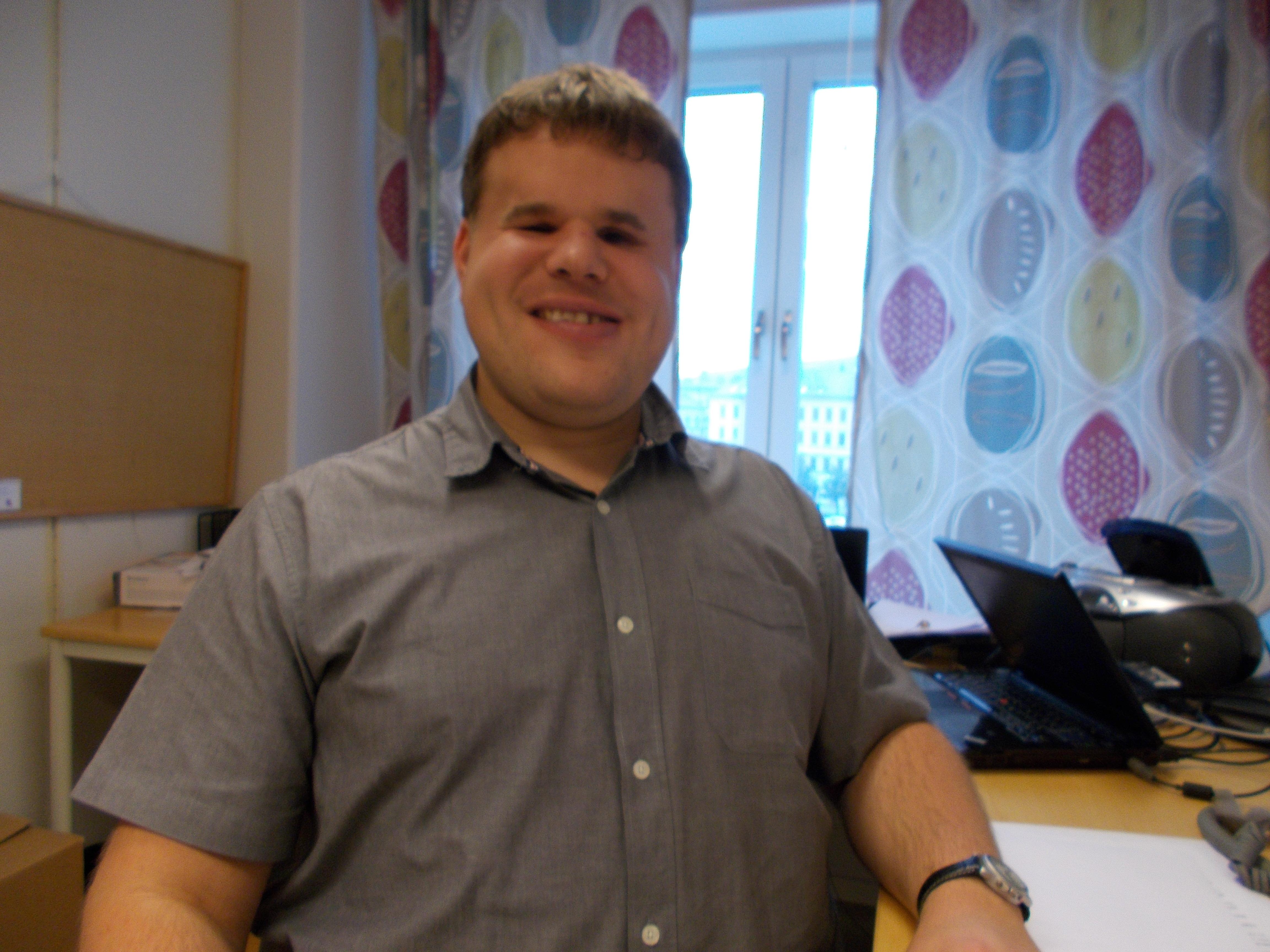 Peter ler mot kameran. Han bär en grå kortärmad skjorta