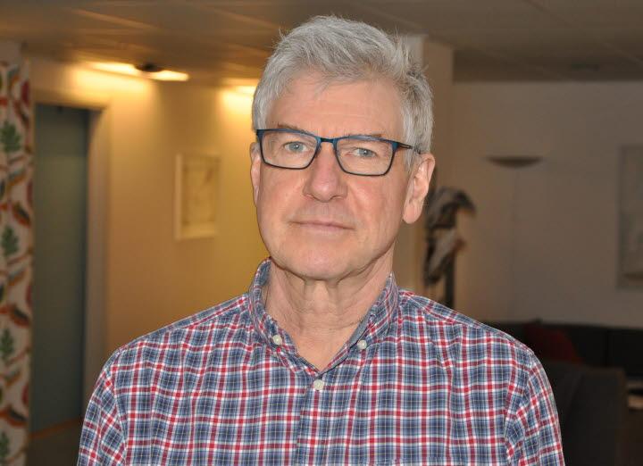 Hans Boman har grått hår och glasögon. Han bär en rutig skjorta