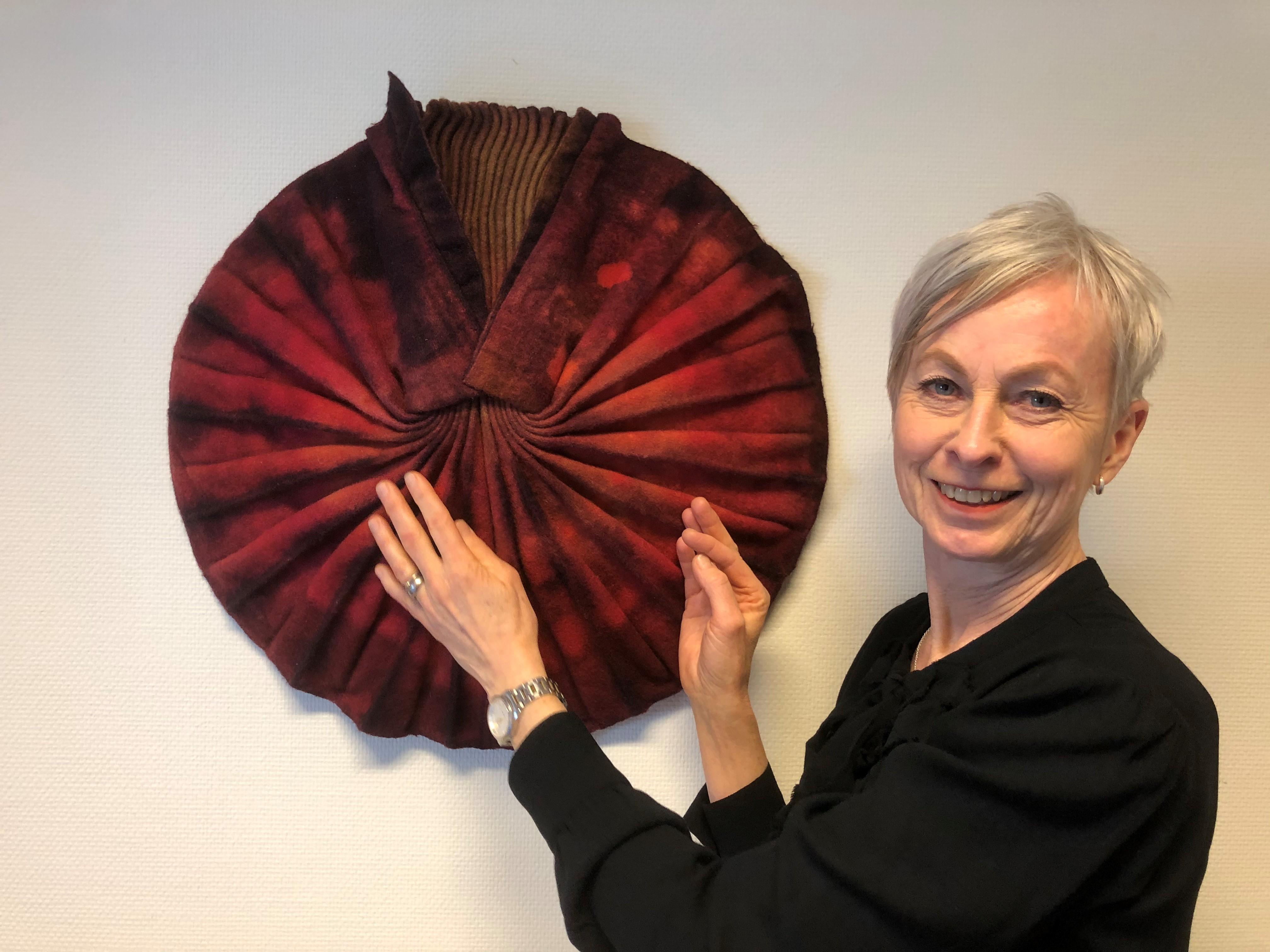 Carina har kortklippt blont hår och posserar framför ett rött taktilt textil konstverk