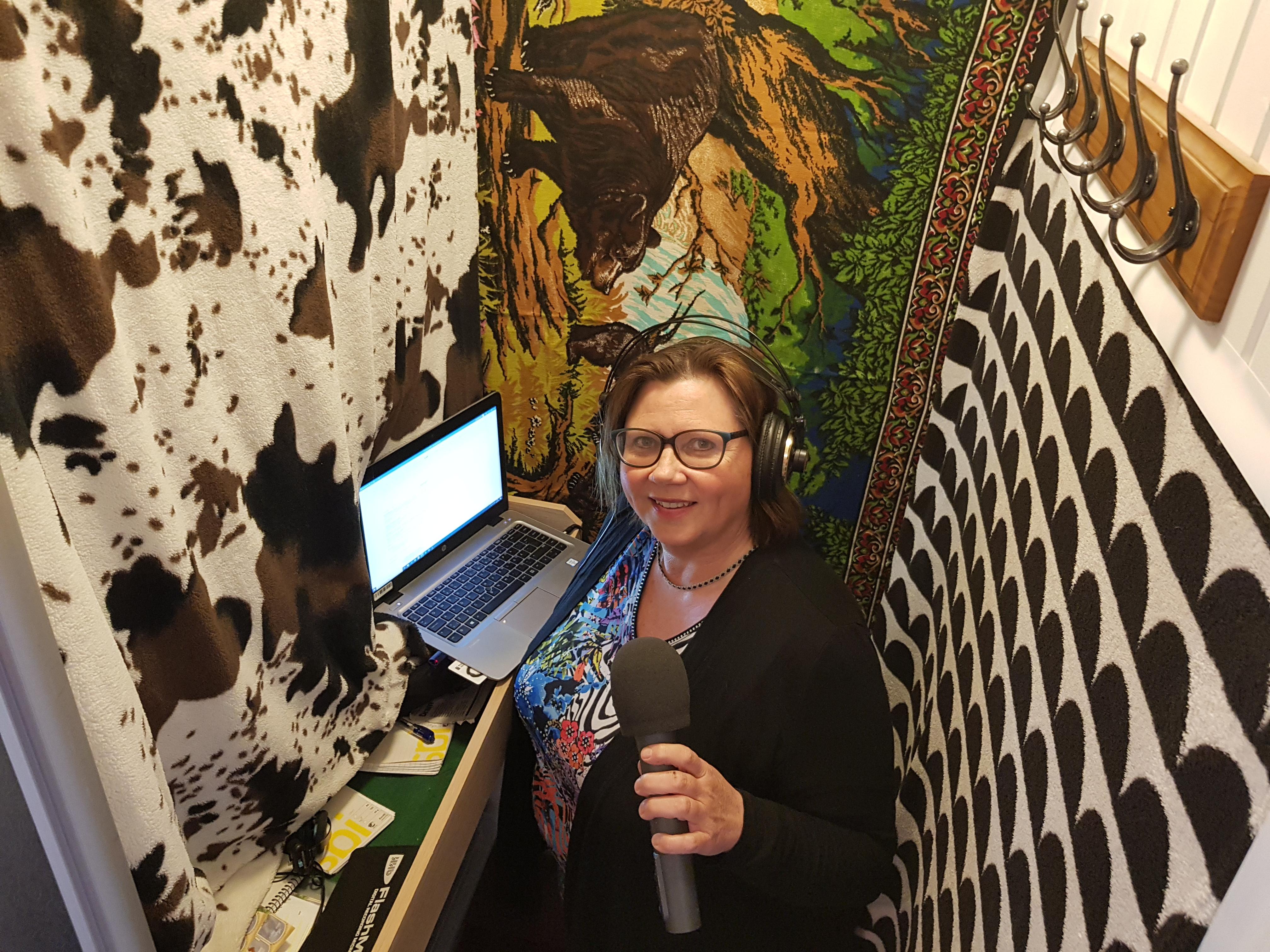 Anette står med mikrofonen i handen inne i sin garderob som har försetts med mjuka plädar på väggarna