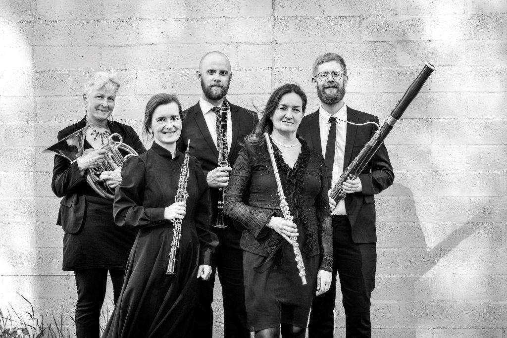 Fem personer med sina blåsinstrument i en svartvit bild