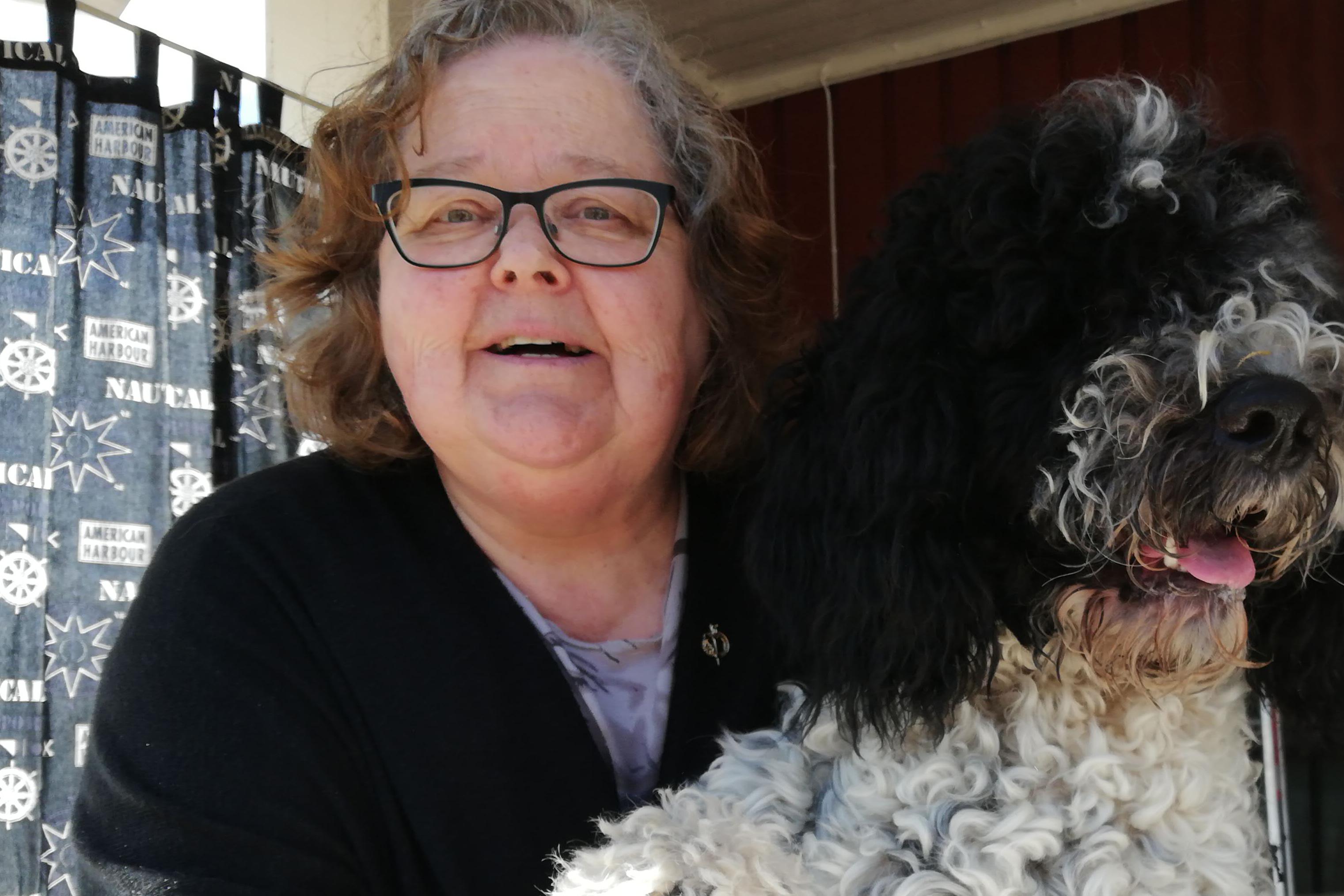 Birgitta har grått hår och glasögon. Hon sitter vid köksbordet med hunden Isak i famnen