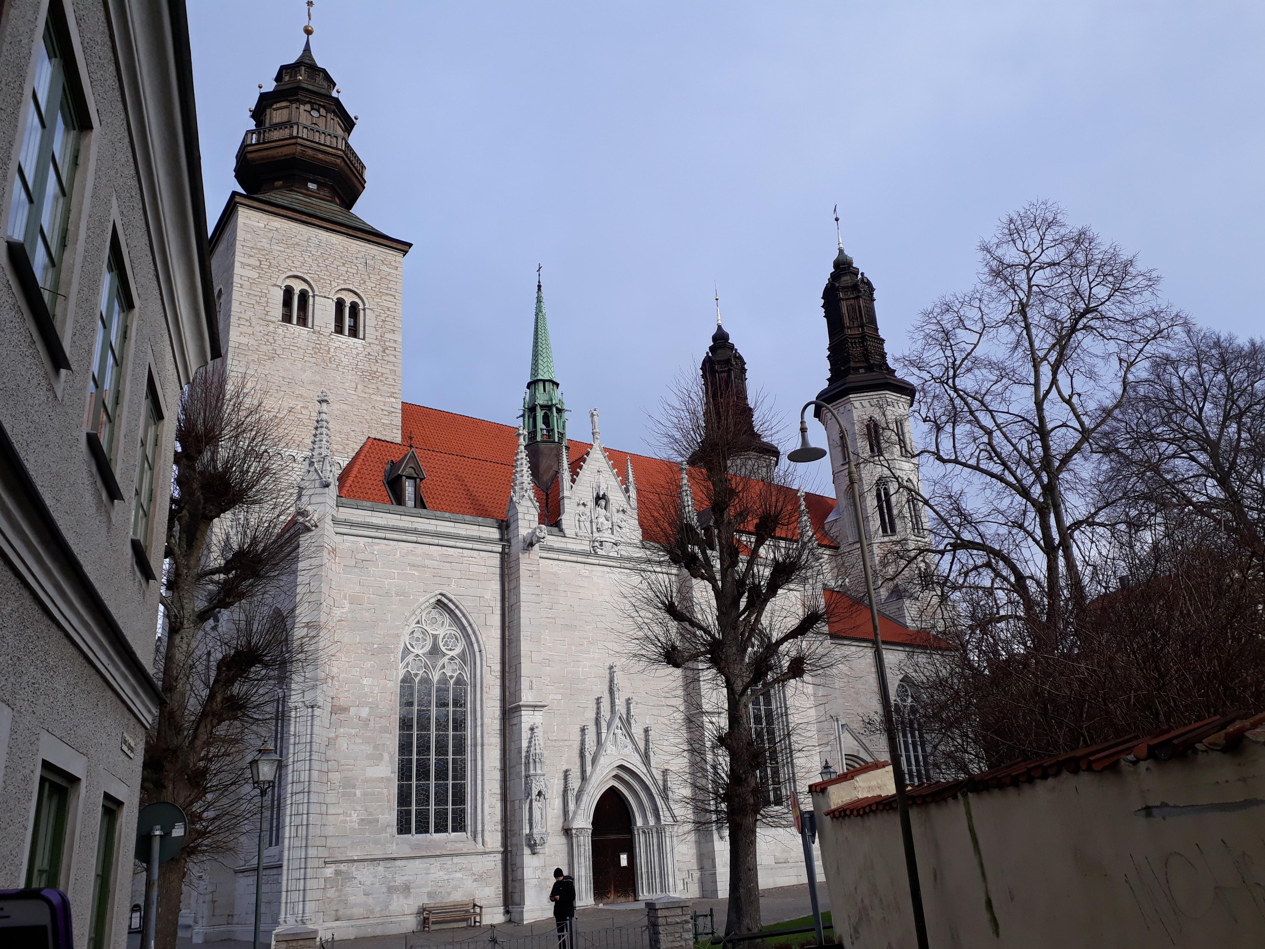 Visby domkyrka är stor och mäktig med vit fasad och tinnar och torn