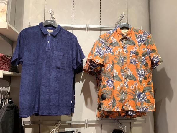 Två kortärmade linneskjortor hänger på galgar i butiken
