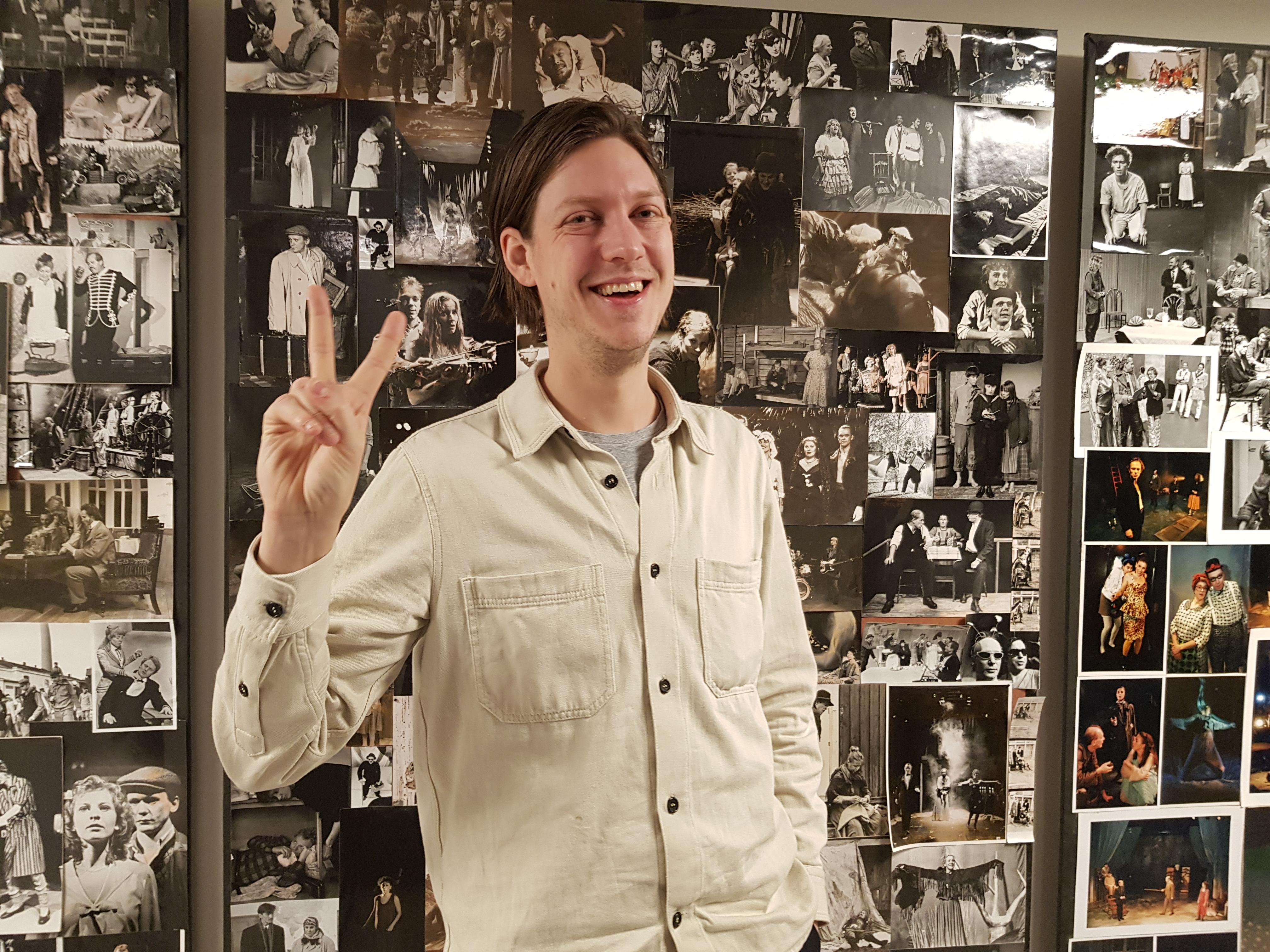 Kristoffer visar segertecken med handen. Han ler stort och sår framför en vägg med teaterbilder