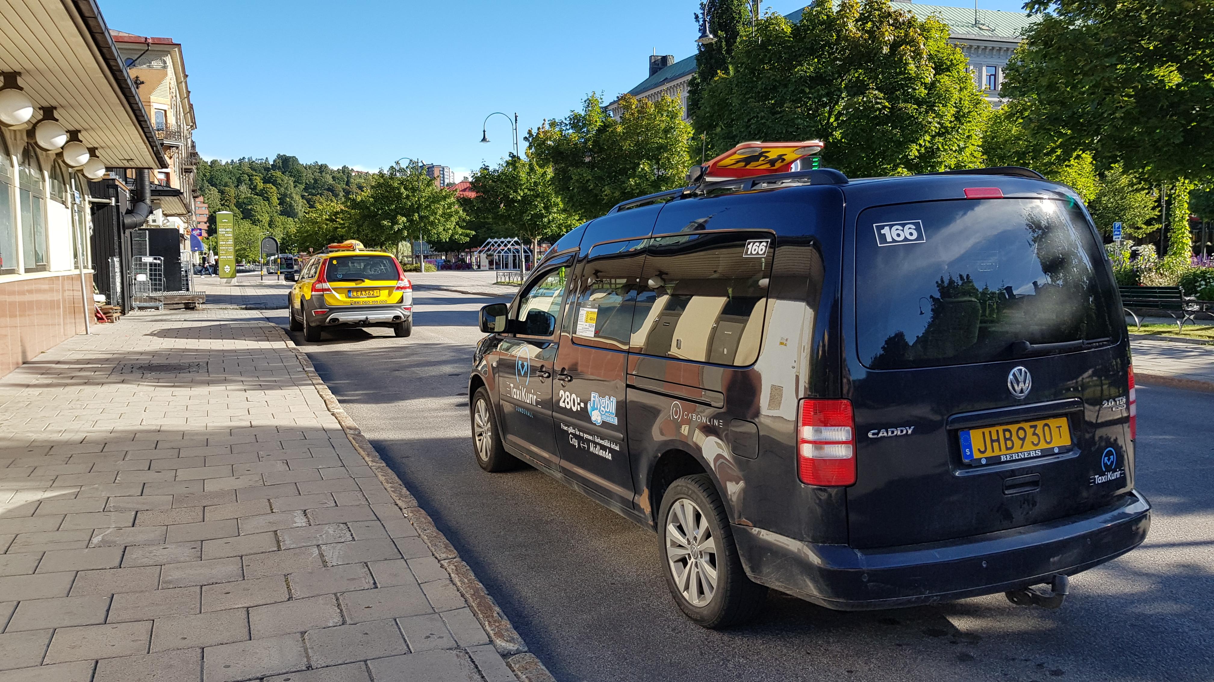 Två taxibilar står vid Taxistationen för att invänta körning