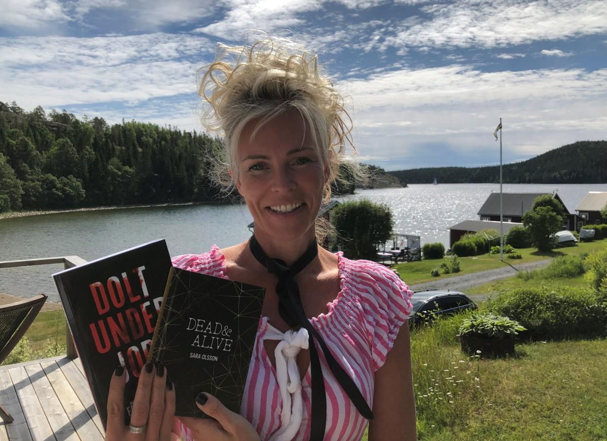 Sara har blond uppsatt hår och en rosa blus. Hon håller upp en av sina böcker. I bakgrunden ser vi Bönhamn och viken