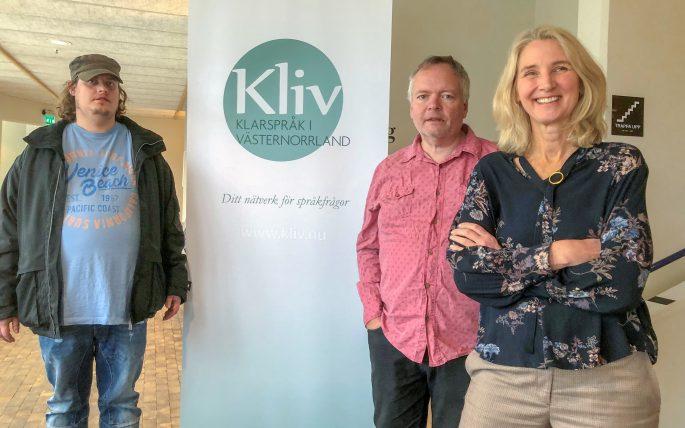 Max, Stefan och Ester framför affischen KLIV - Klarspråk i Västernorrland